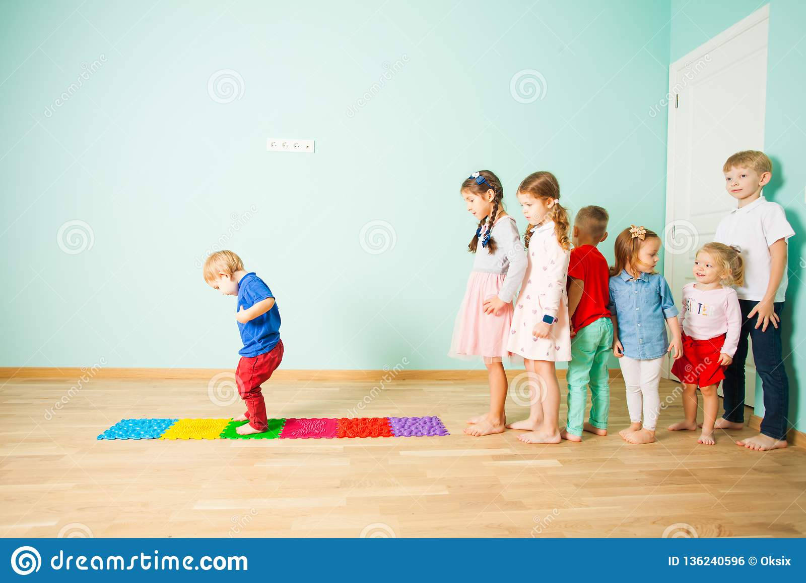 I bambini stanno a piedi nudi in una fila fra le stuoie di massaggio