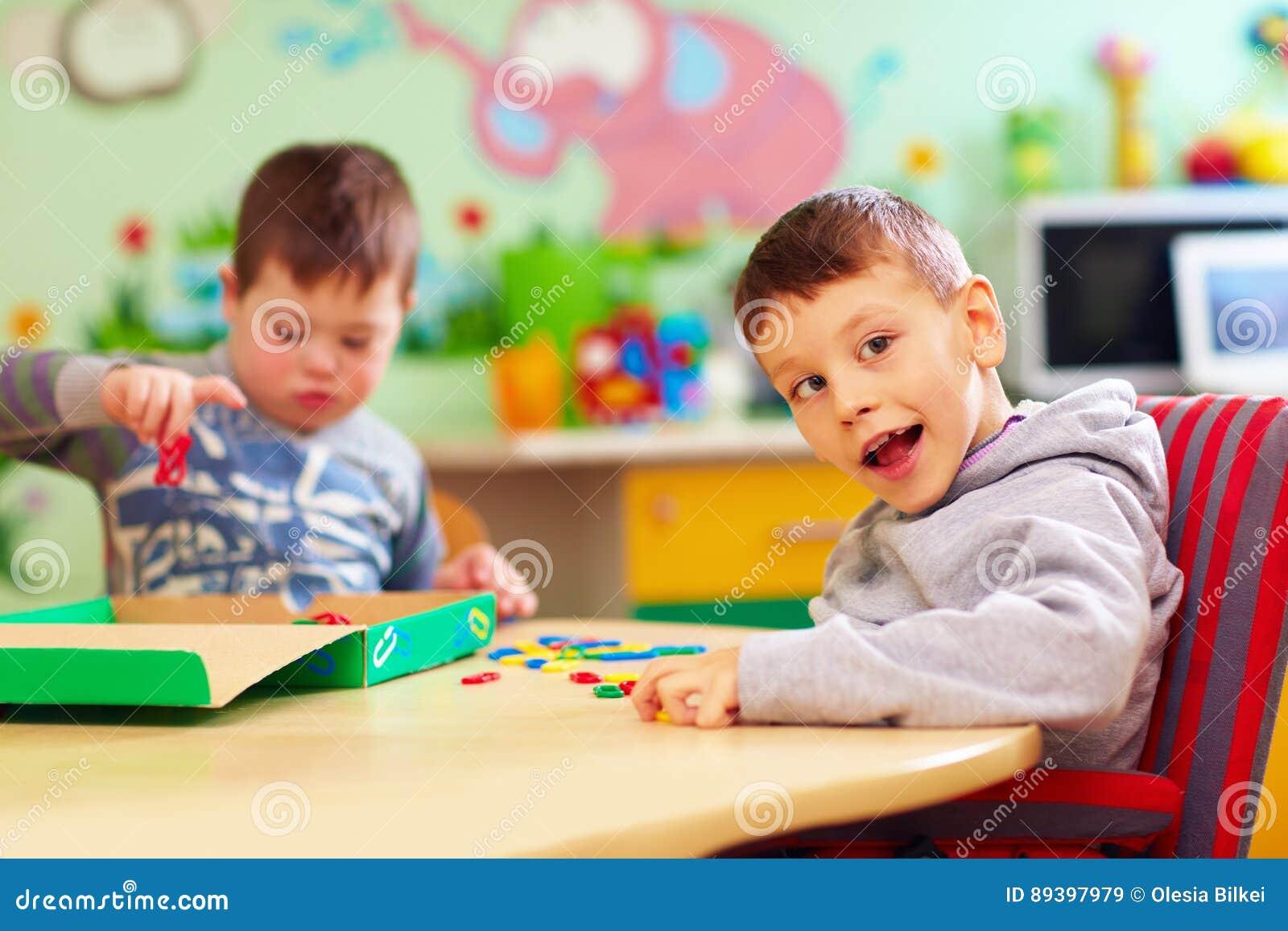 I bambini svegli con i bisogni speciali che giocano con lo sviluppo gioca mentre si siedono allo scrittorio nell asilo