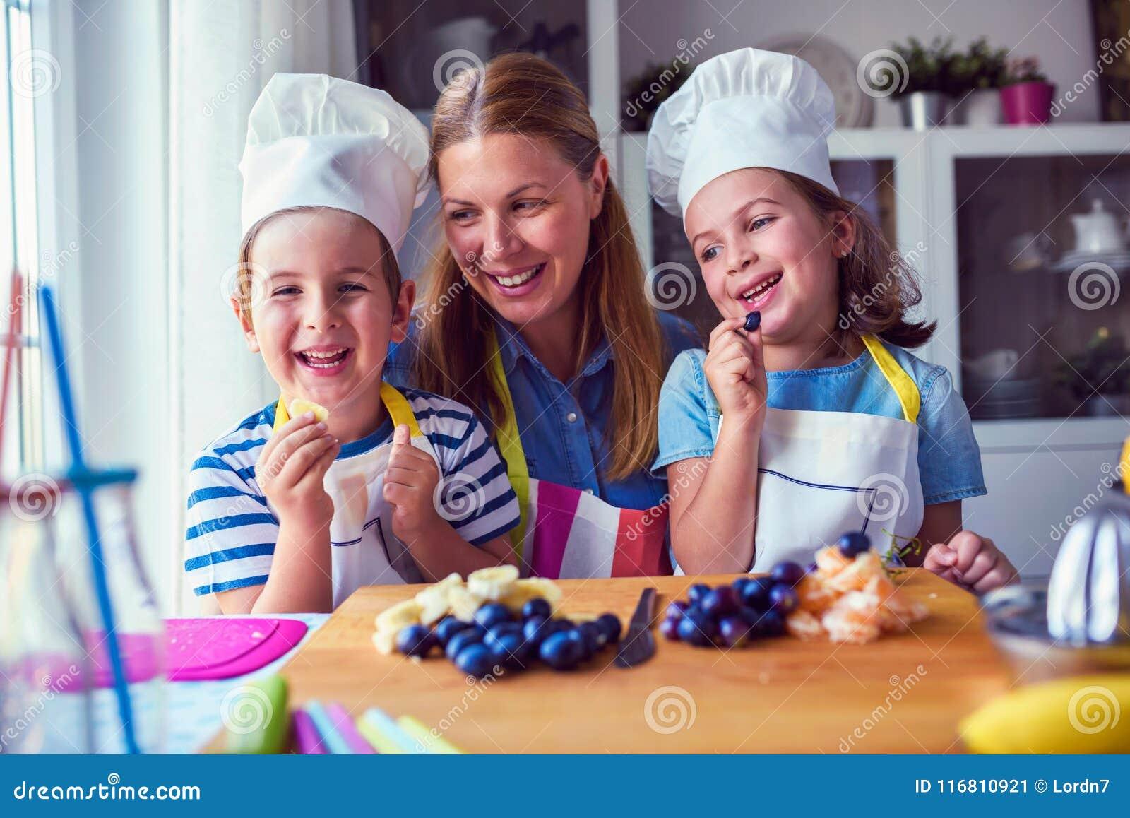 I bambini svegli con la madre che prepara una frutta sana fanno un spuntino in cucina