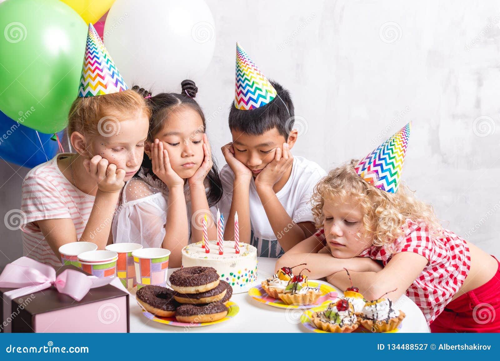 I bambini turbati si sono riuniti intorno alla tavola e ad esaminare il dolce saporito