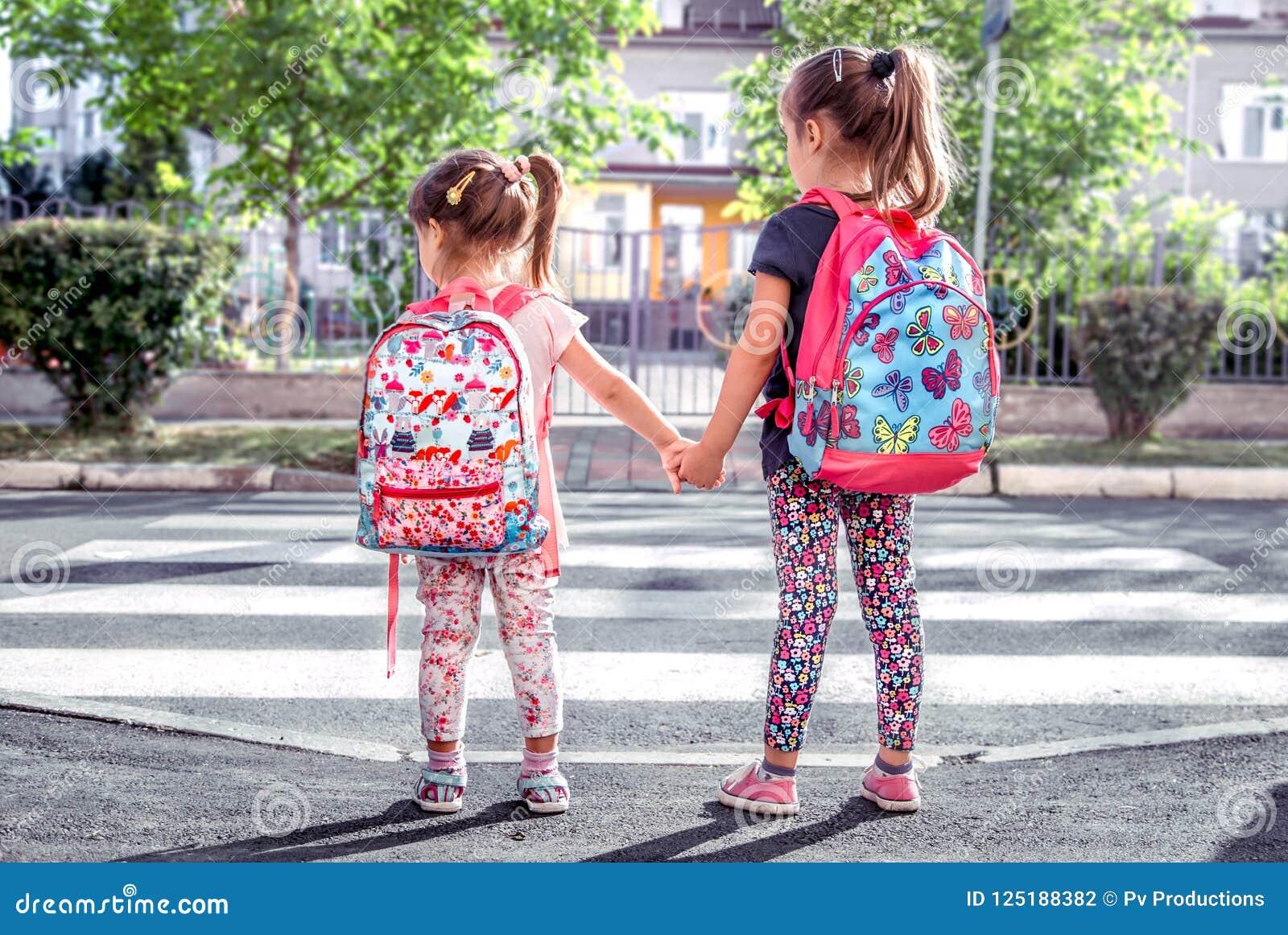 I bambini vanno a scuola, studenti felici con gli zainhi e tenersi per mano della scuola insieme