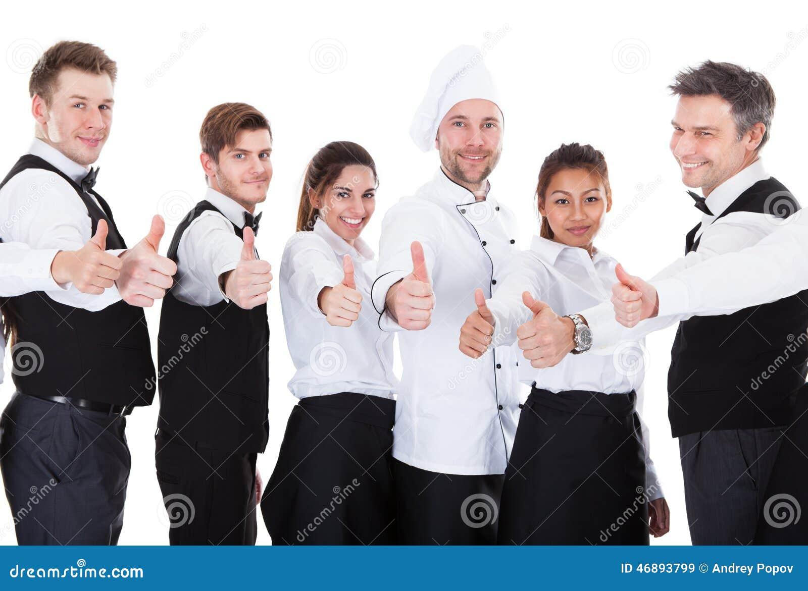 I camerieri e le cameriere di bar che mostrano i pollici aumentano il segno