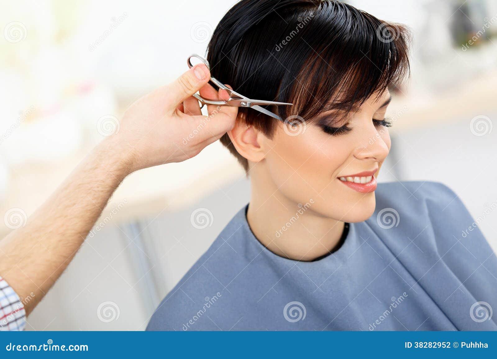 I capelli di Cutting Woman del parrucchiere nel salone di bellezza. Taglio di capelli