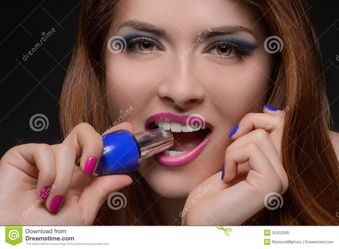 I choose the blue one! Portrait of beautiful women holding a nail polish in her teeth