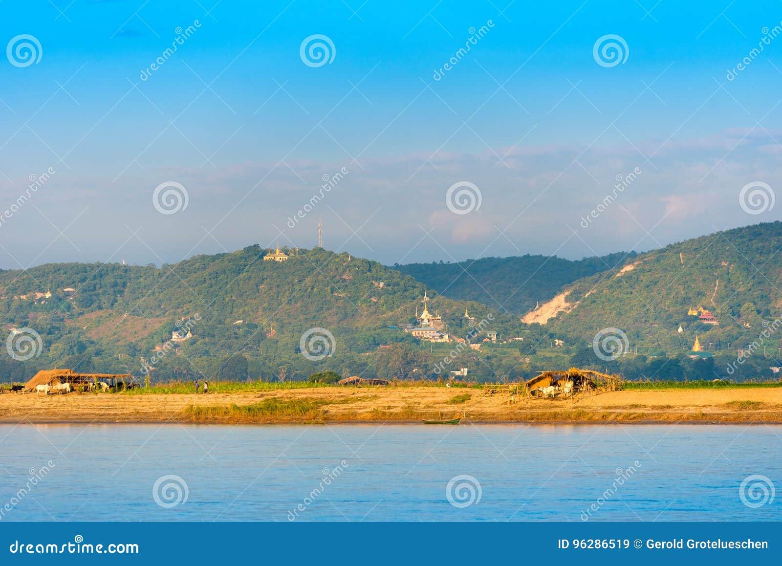 I contadini che lavorano alla banca del fiume Irrawaddy, Mandalay, Myanmar, Birmania Copi lo spazio per testo verticale
