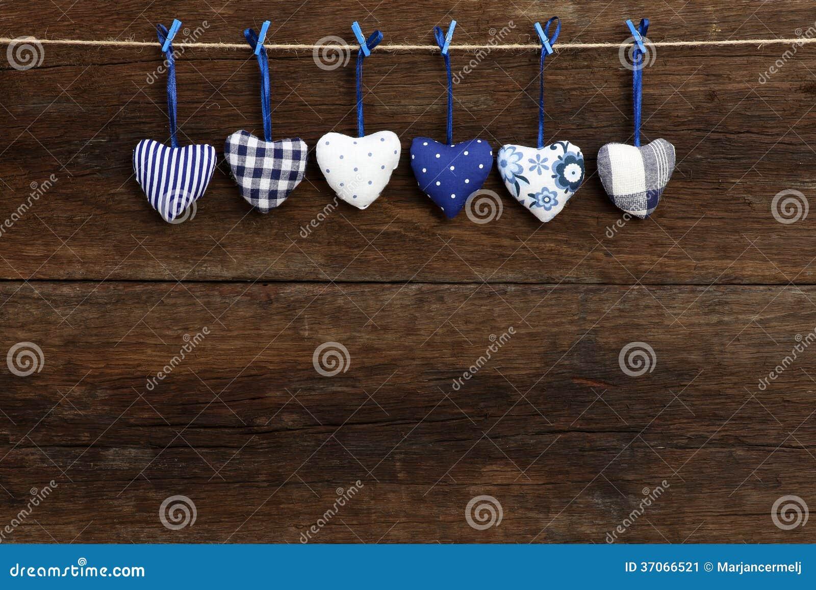 I cuori del modello del percalle del biglietto di S. Valentino blu di amore che appendono sulla t di legno