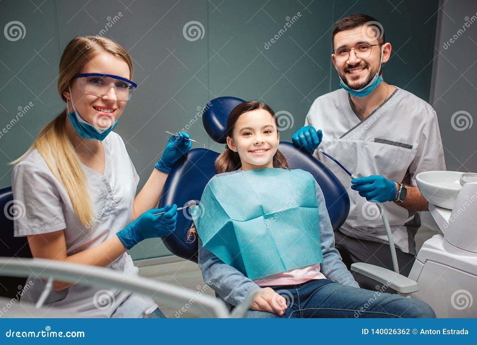 I detists piacevoli allegri della donna del giovane si siedono e posano con il bambino in sedia dentaria Gli adulti tengono gli s