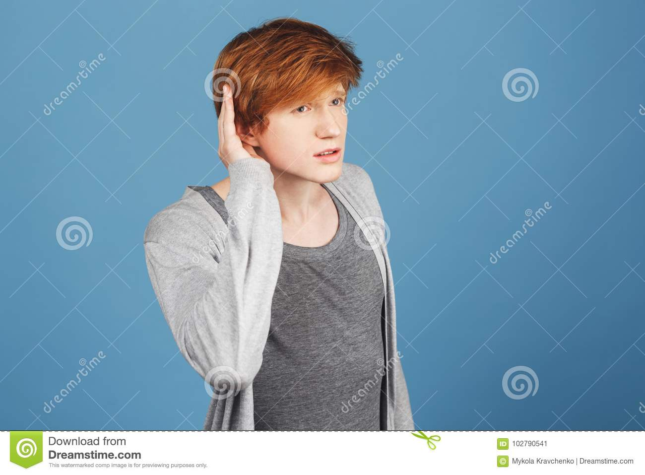 I don`t hear you. Copy space. Close up of serious good-looking guy with red hair in casual clothes holding hand near ear