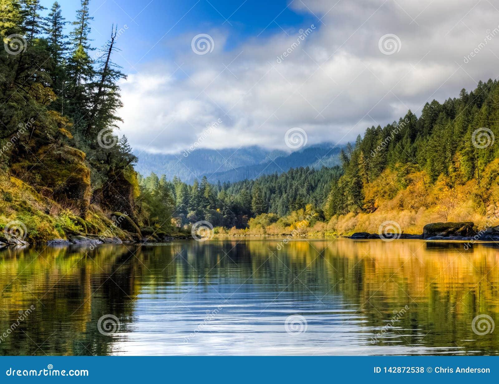 I forti massi muscosi allineano i bordi di Rogue River più basso alla fine d ottobre con cielo blu e le nuvole nella distanza