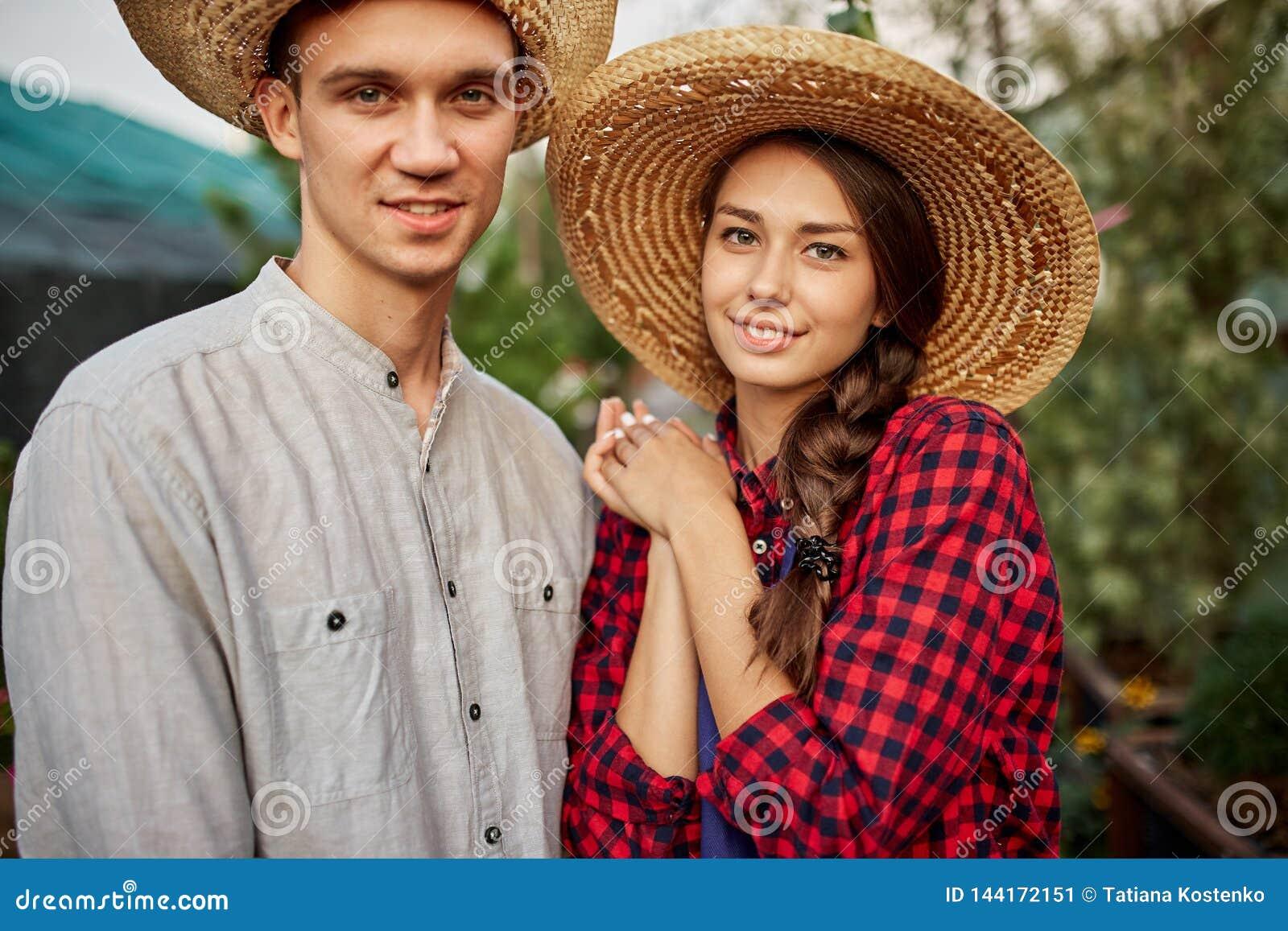 I giardinieri della ragazza e del tipo in cappelli di paglia stanno insieme in giardino un giorno soleggiato