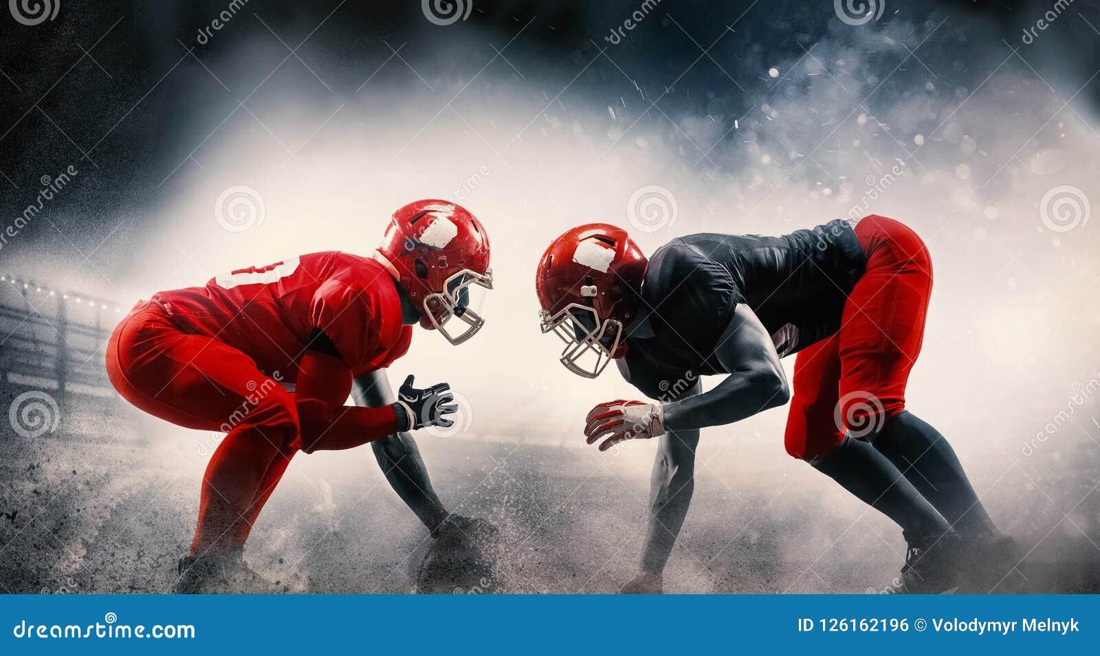 I giocatori di football americano nell azione giocano nello stadio dello sport professionale