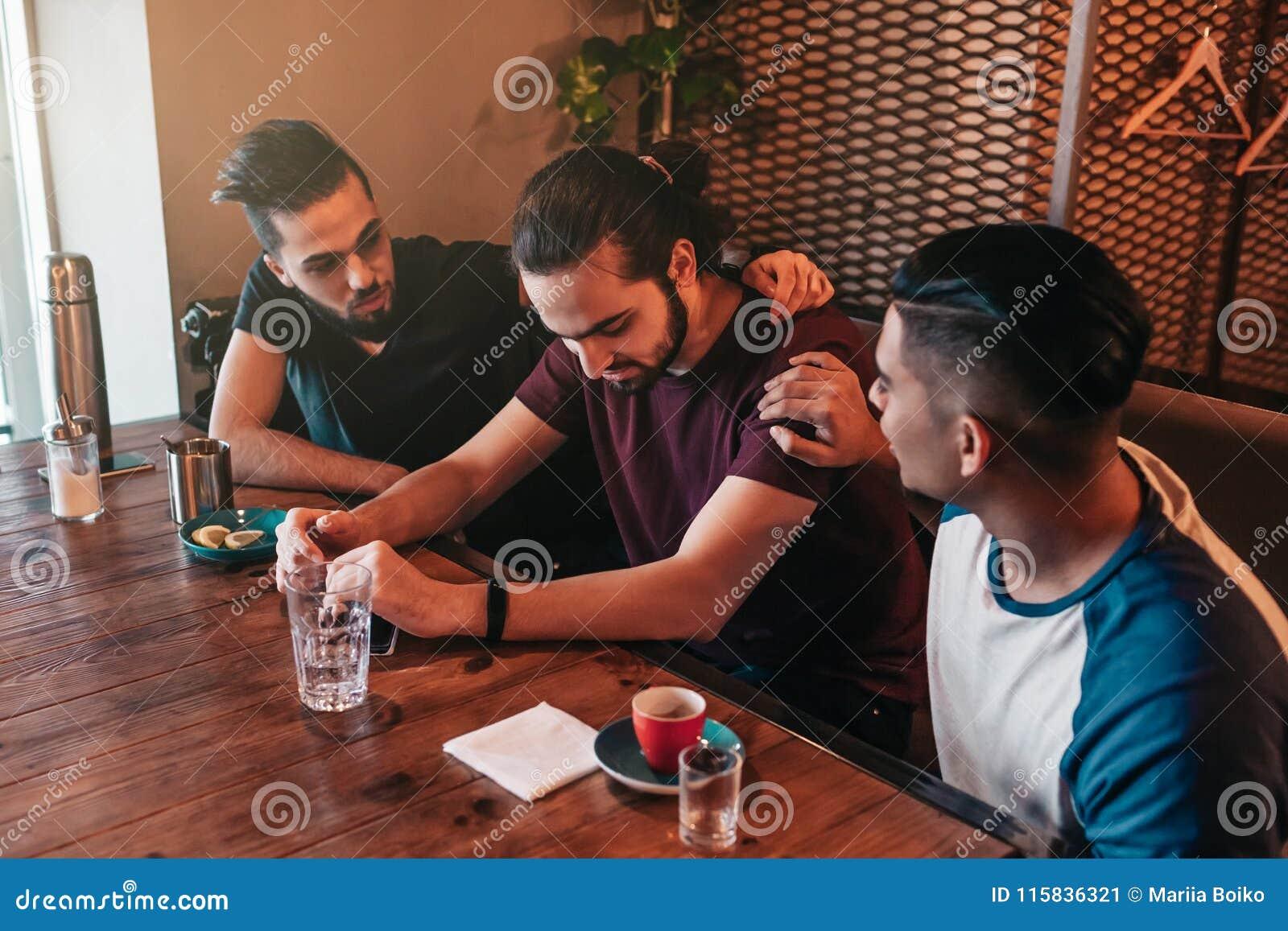 I giovani complementari incoraggiano il loro amico dal cuore infranto I tipi arabi lo incoraggiano su in ristorante Concetto di a