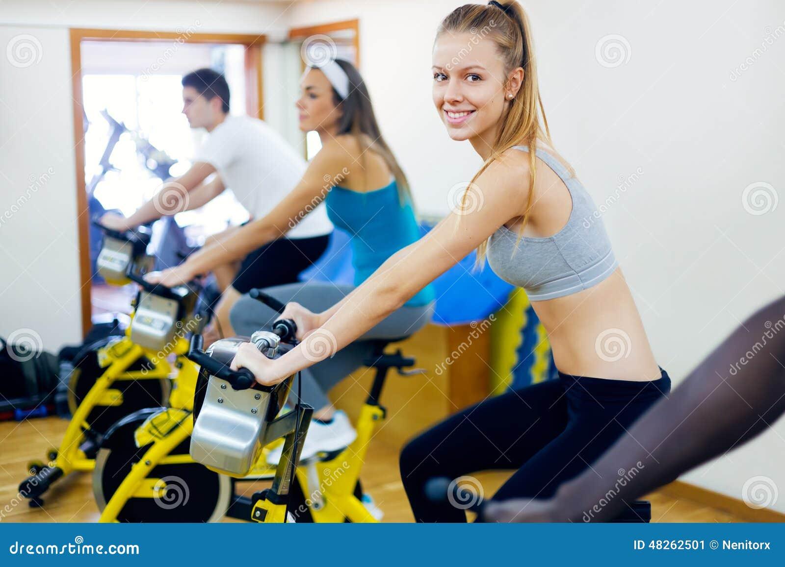 I giovani con forma fisica vanno in bicicletta nella palestra