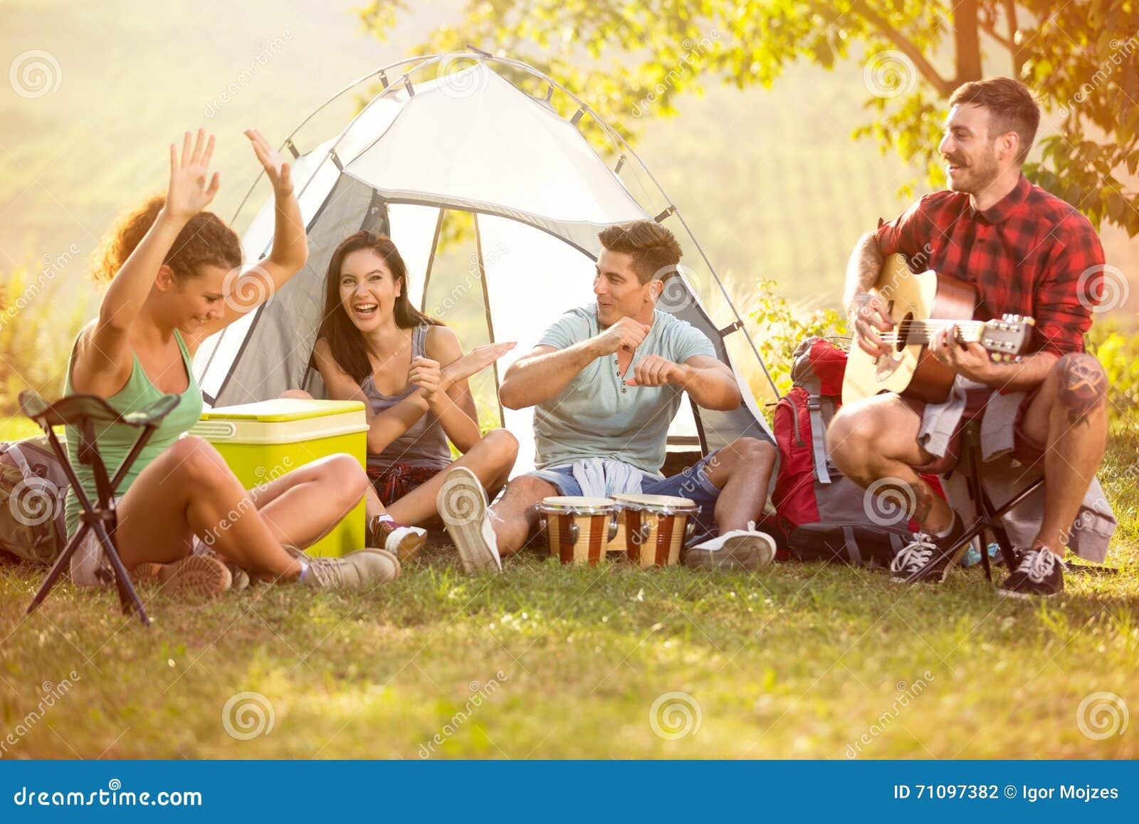 I giovani godono di nella musica dei tamburi e della chitarra sul viaggio di campeggio