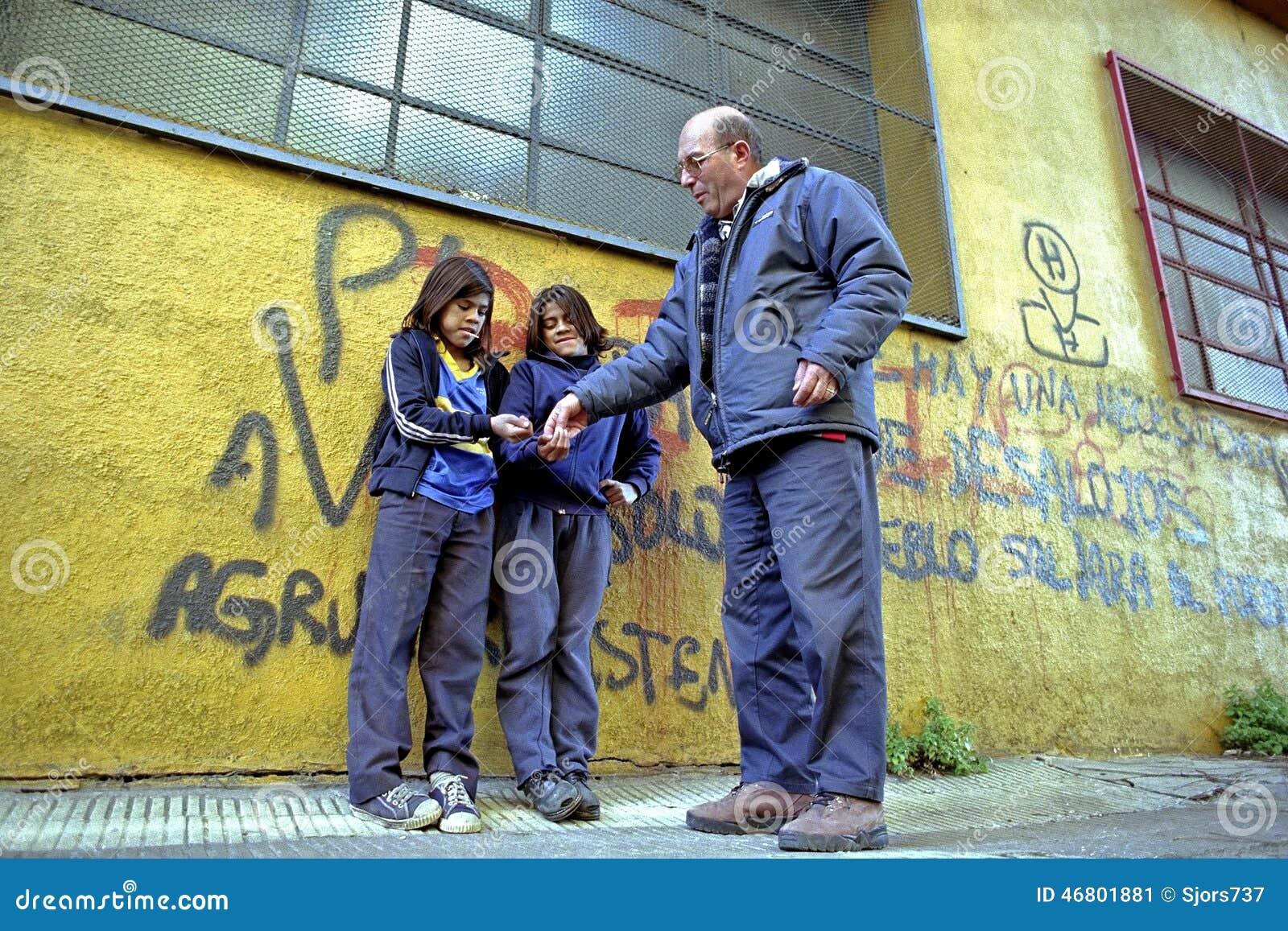 I giovani mendicanti ottengono i soldi da un lavoratore della via