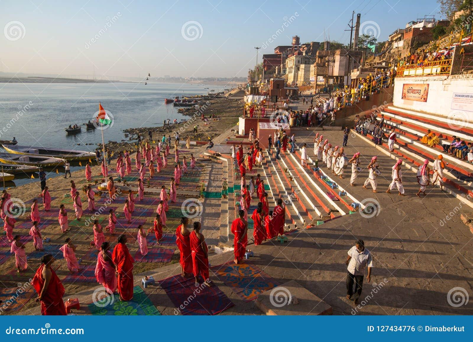 I giovani monaci indù conducono una cerimonia per incontrare l alba sulle banche di Gange ed alzano la bandiera indiana