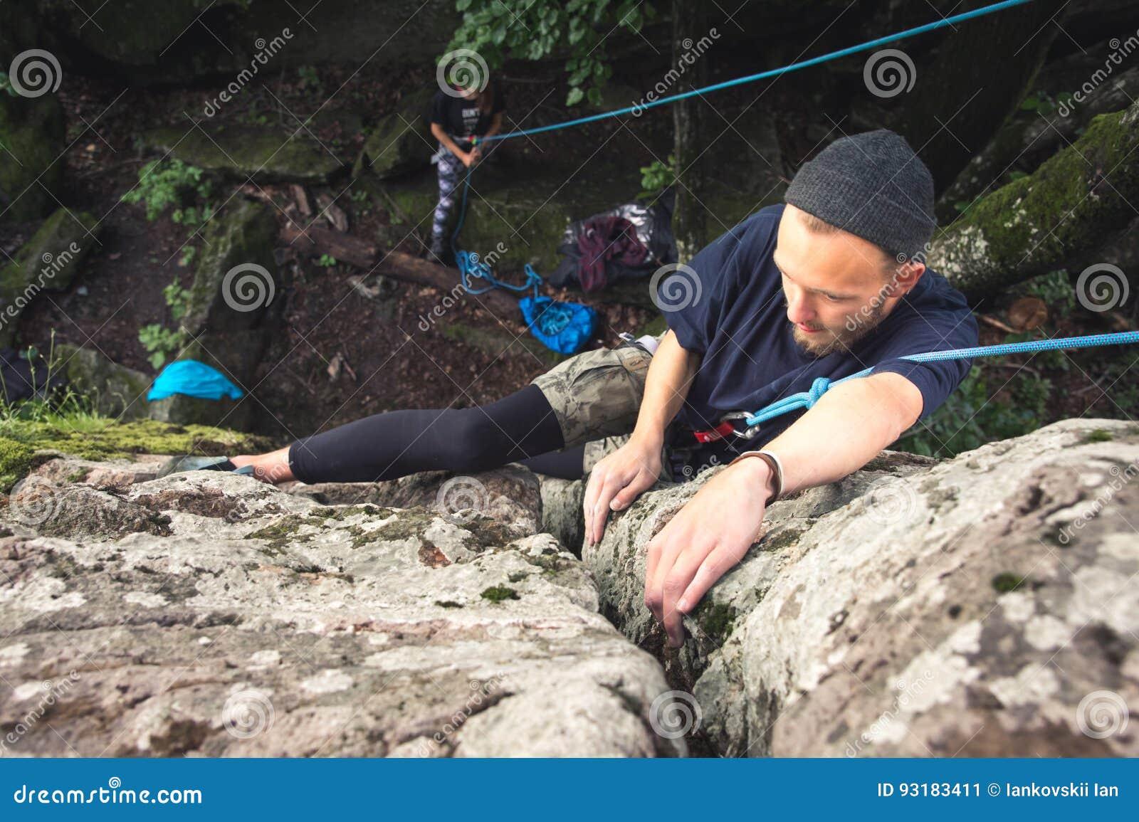 I giovani pantaloni a vita bassa sono impegnati in arrampicata con assicurazione sulle rocce con muschio verde