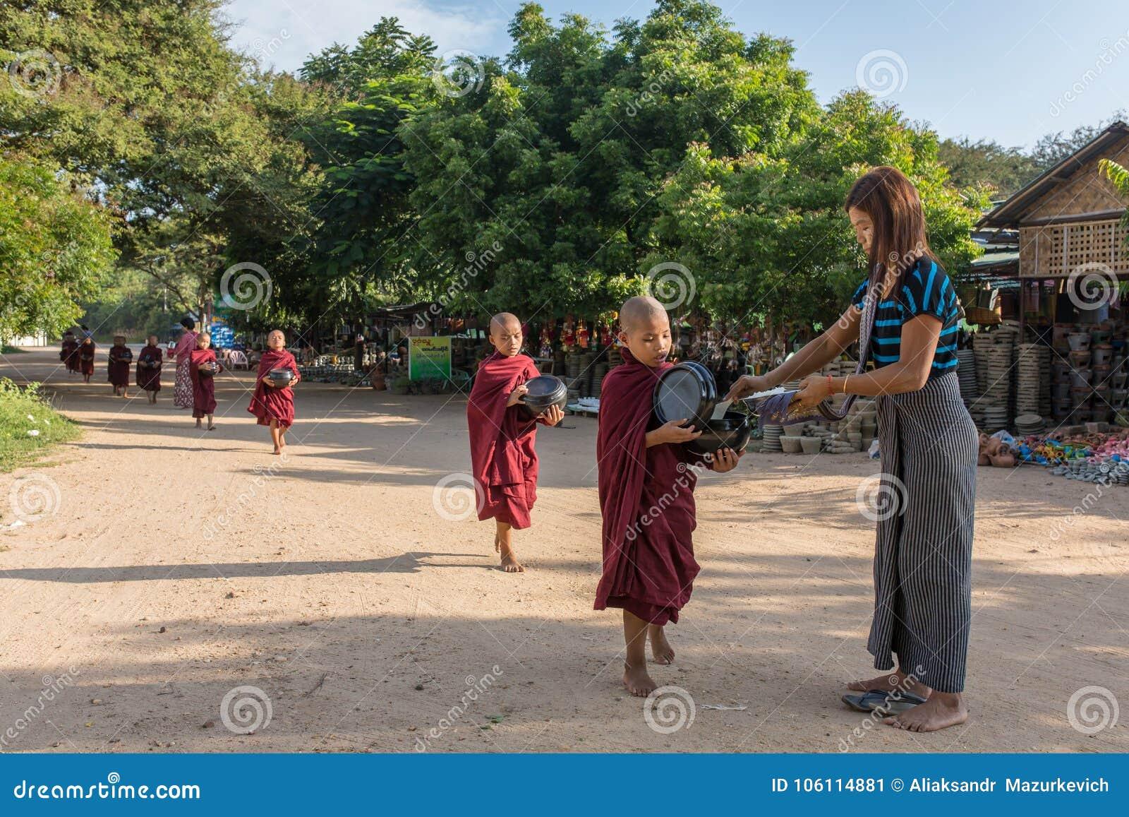I giovani principianti buddisti camminano per raccogliere le elemosine e le offerti sulle vie di Bagan, Myanmar
