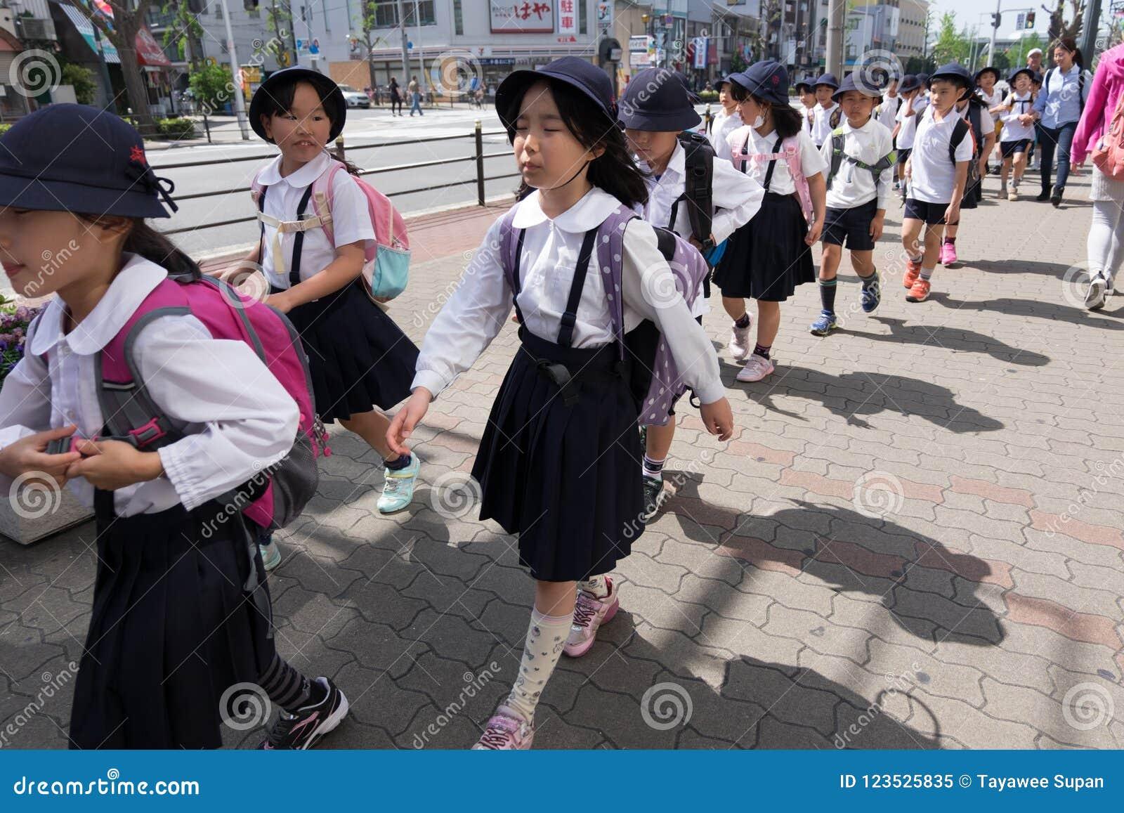 I giovani studenti elementari giapponesi stanno avendo escursione in Osak