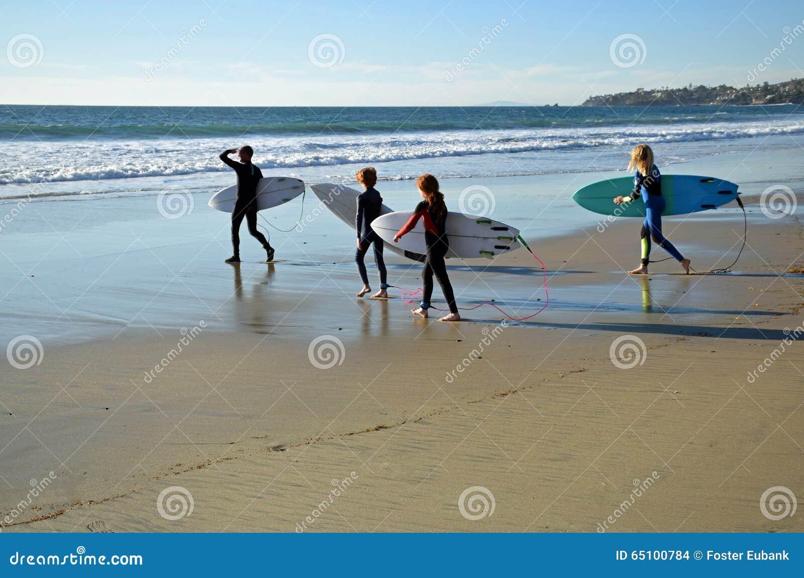 I giovani surfisti si dirigono verso la spuma alla - Alla colorazione della spiaggia ...