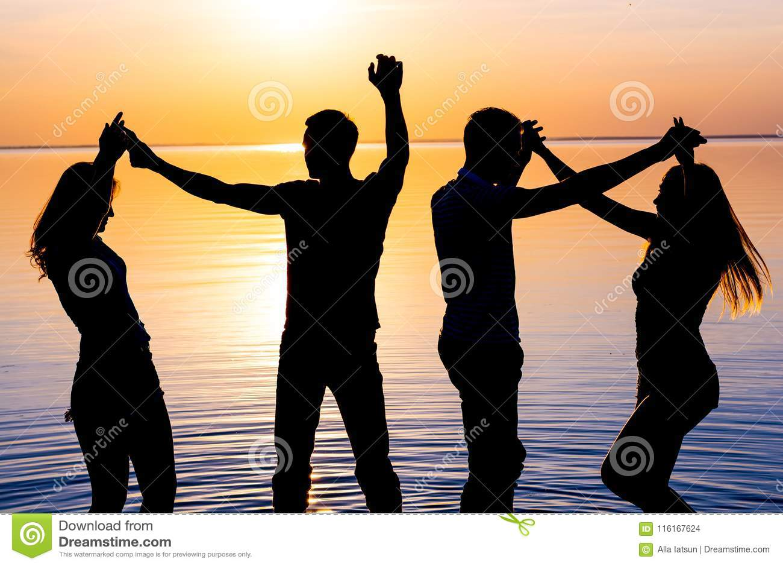 I giovani, i tipi e le ragazze stanno ballando le coppie al backg del tramonto
