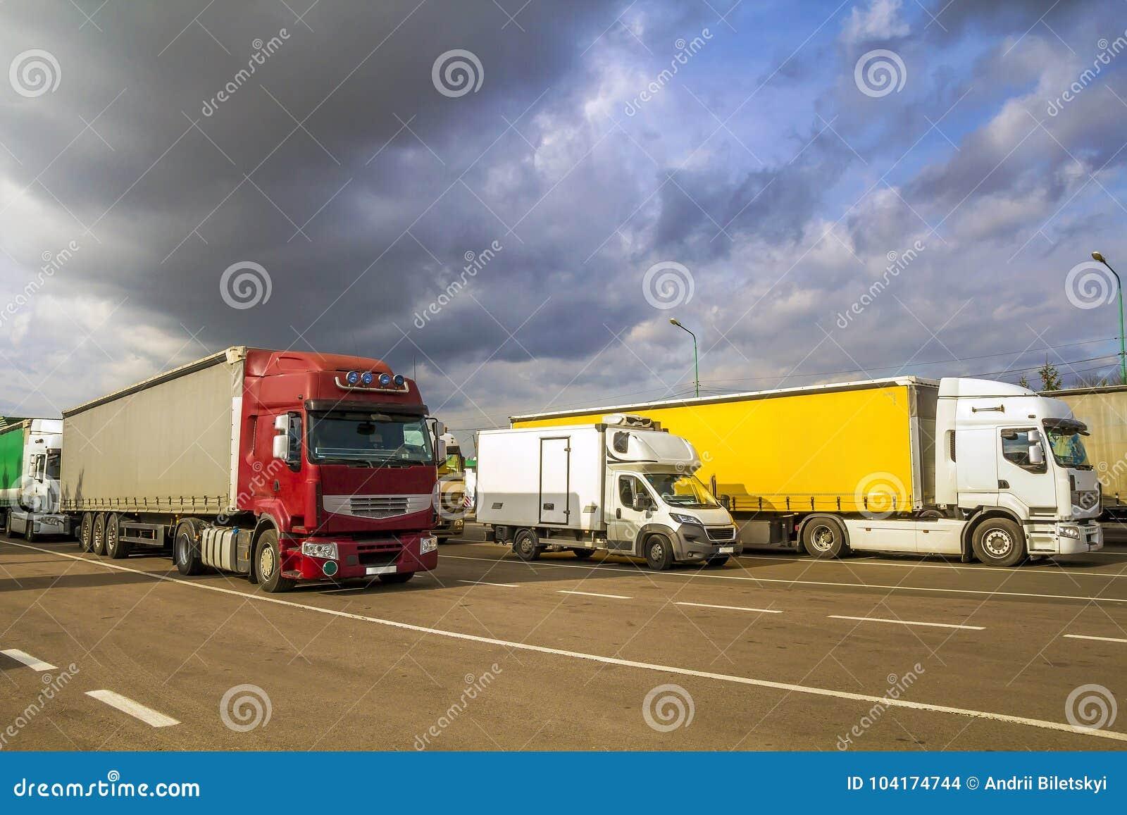 I grandi semi-camion moderni variopinti ed i rimorchi di differente fa