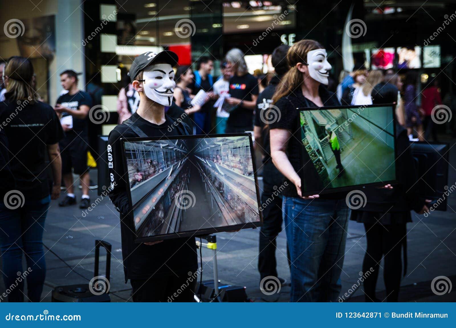 I gruppi di persone messi sulla maschera anonima e tengono il monitor dello schermo per dividere le informazioni su crudeltà dell