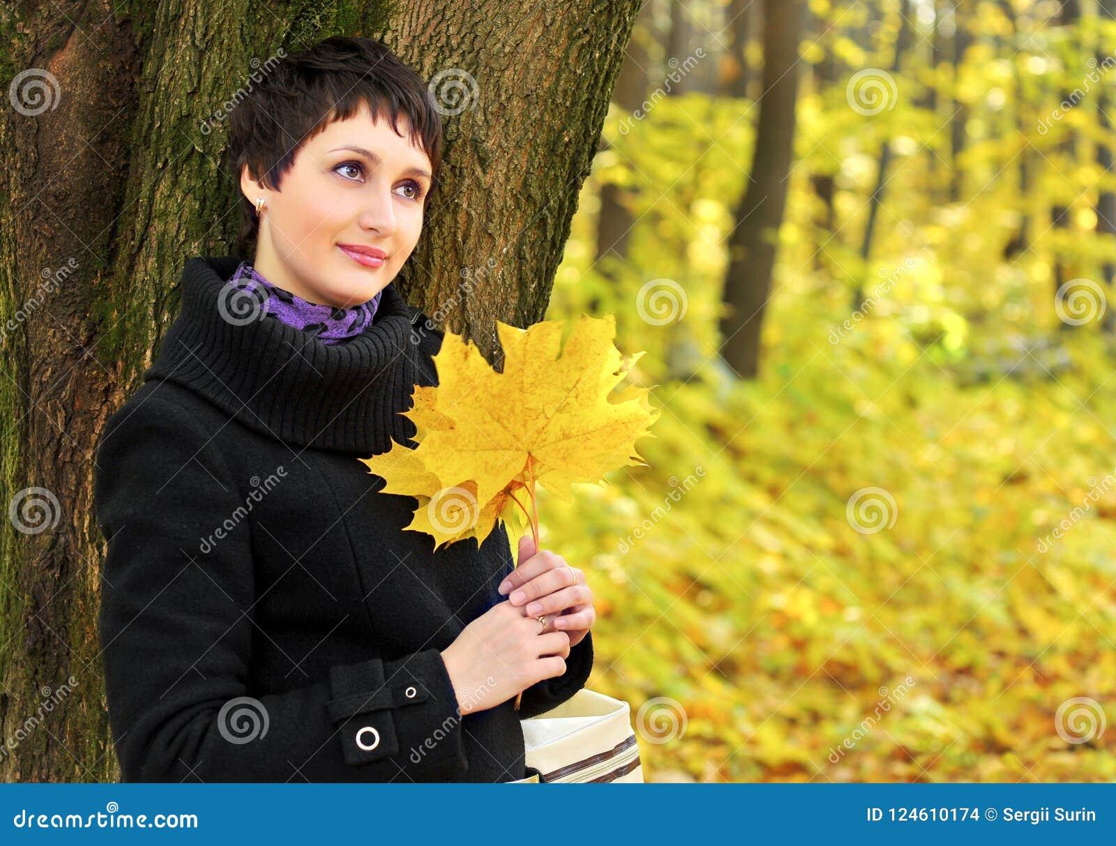 I höstkvinna nära trädstammen som rymmer en bukett av lönnlöv
