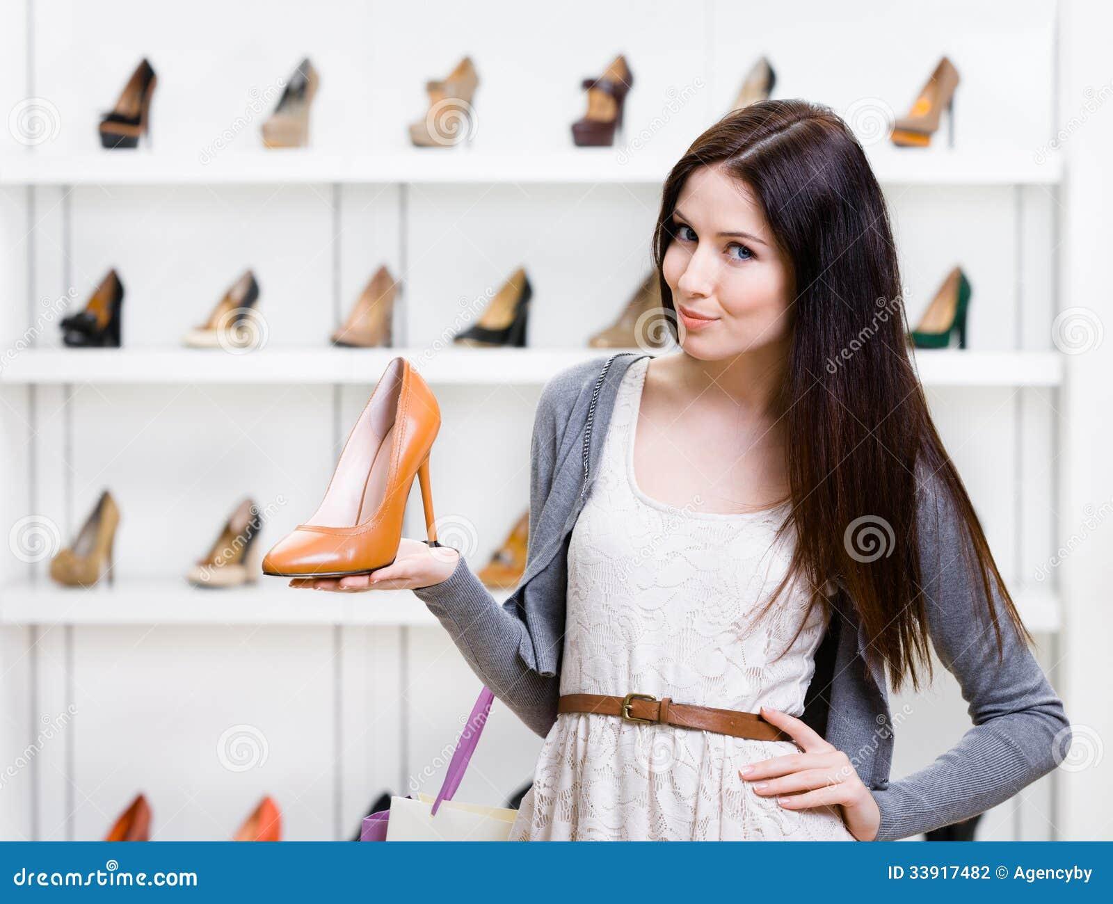 I halvfigur stående av kvinnan som håller skon