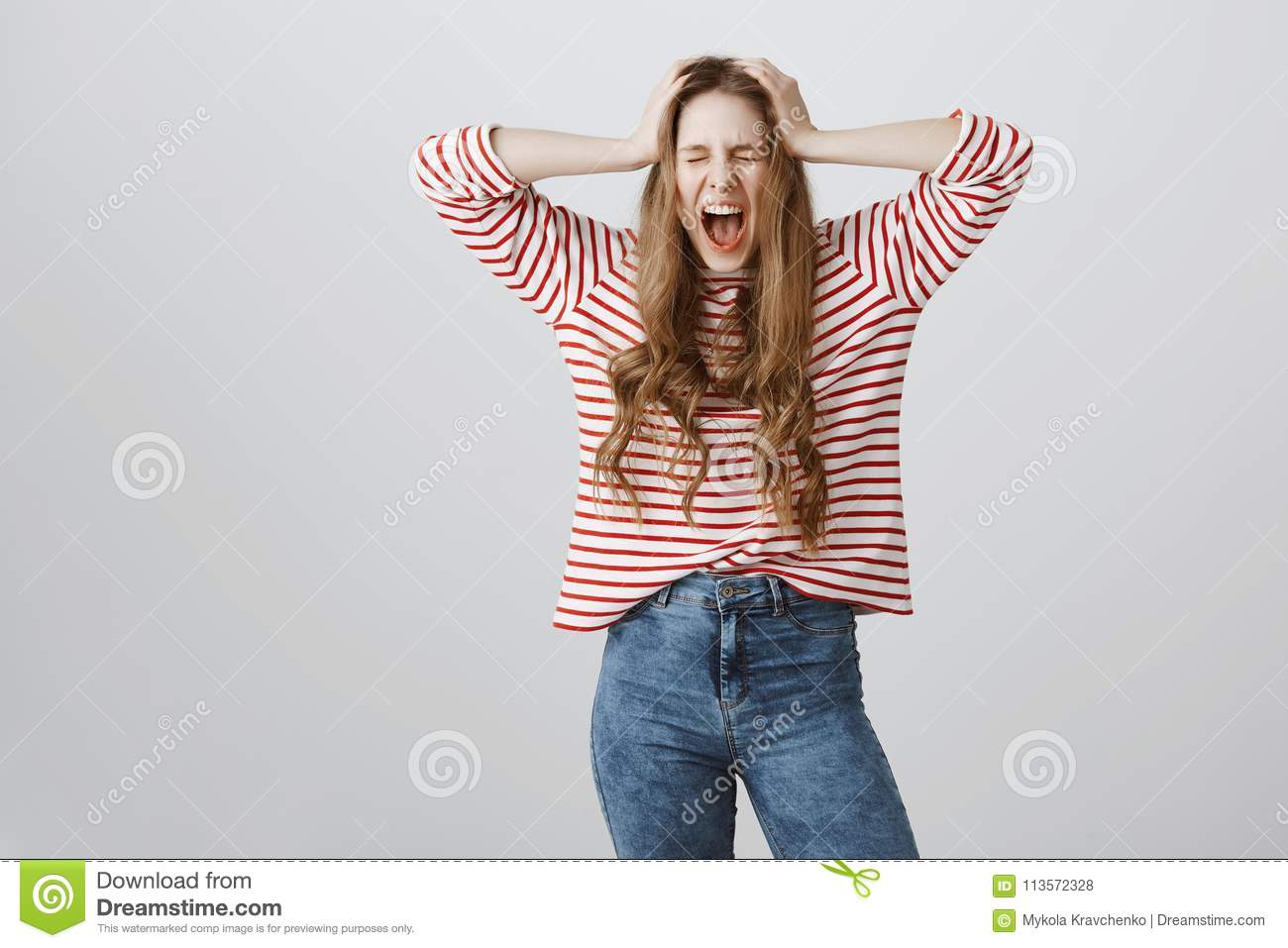 I hate adults. Portrait of depressed and angry european teenage girl screaming with closed eyes and holding hands on