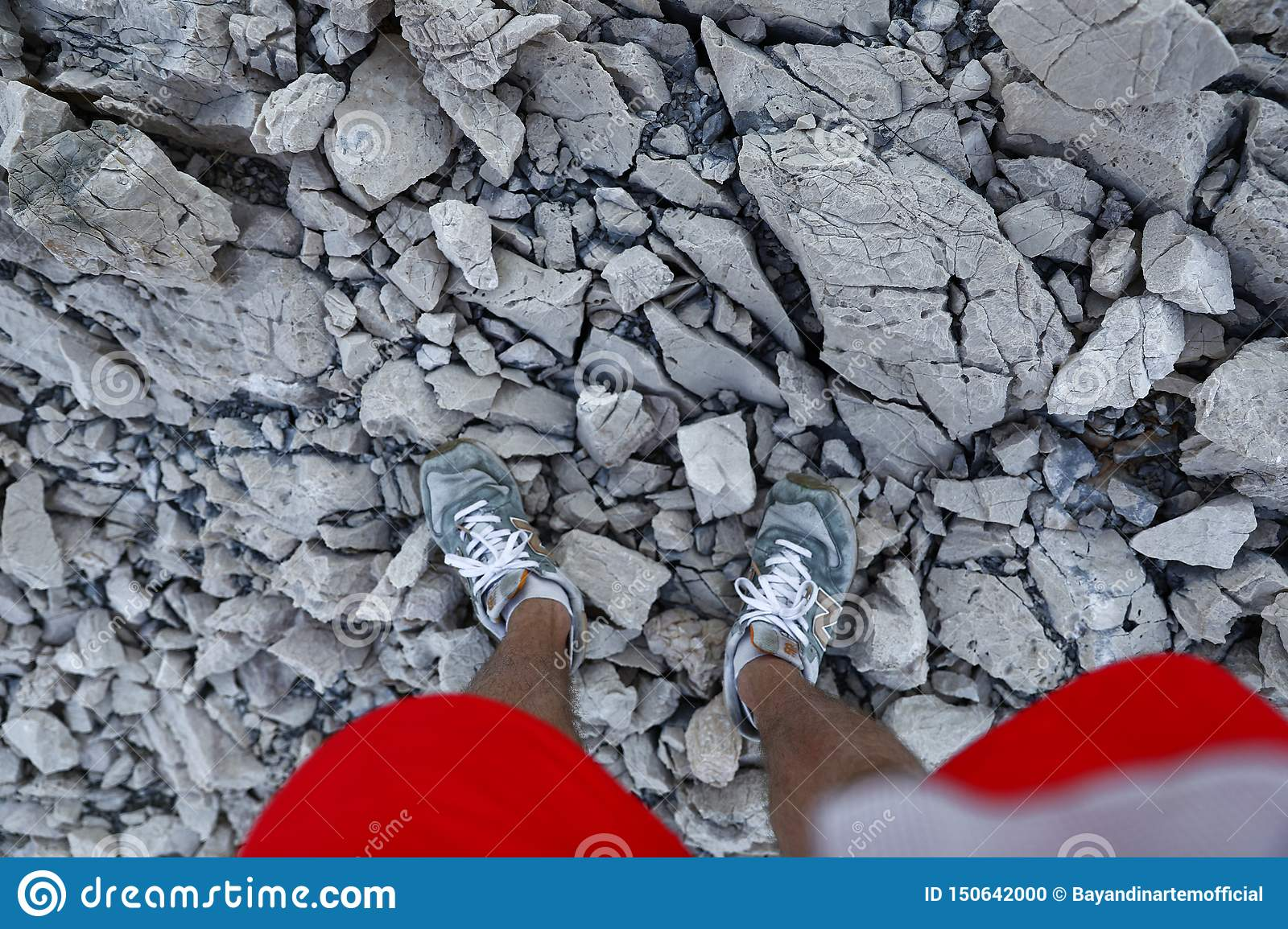 Legs in sport shoes and red shorts on the rocky path in the mountains
