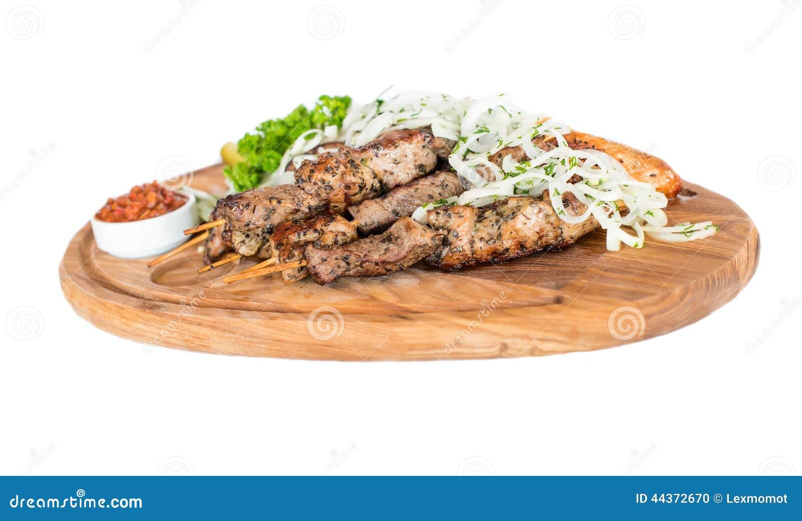I kebab arrostiti col barbecue sani della carne di maiale cubati magra sono servito con una tortiglia di cereale e un insalata fr