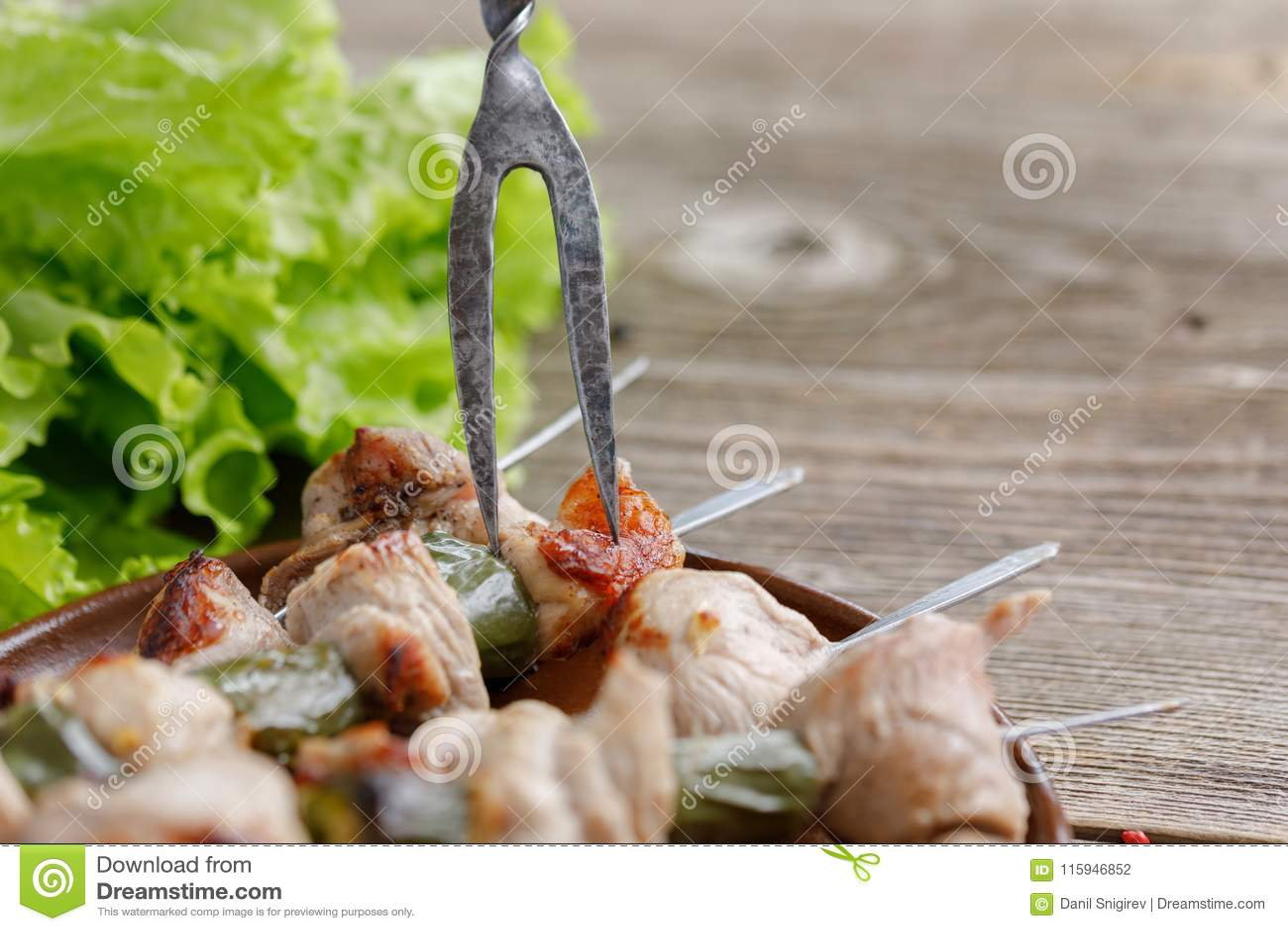 I kebab delicati della carne di maiale cucinati su un fuoco aperto con una forcella squisita hanno attaccato in loro natura morta