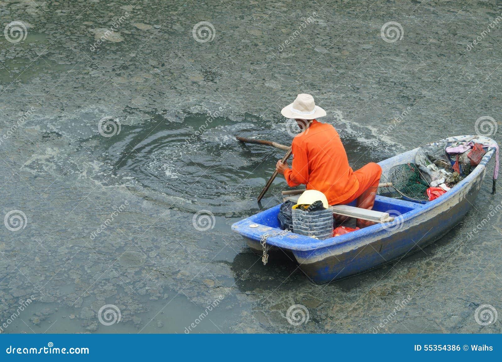 I lavoratori di risanamento puliscono i rifiuti nel fiume