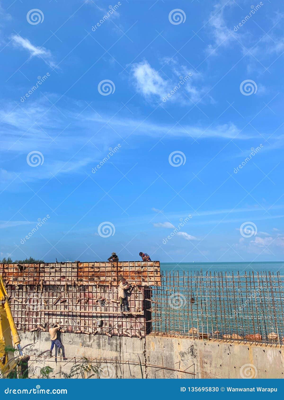 I lavoratori stanno lavorando per costruire la strada lungo la spiaggia