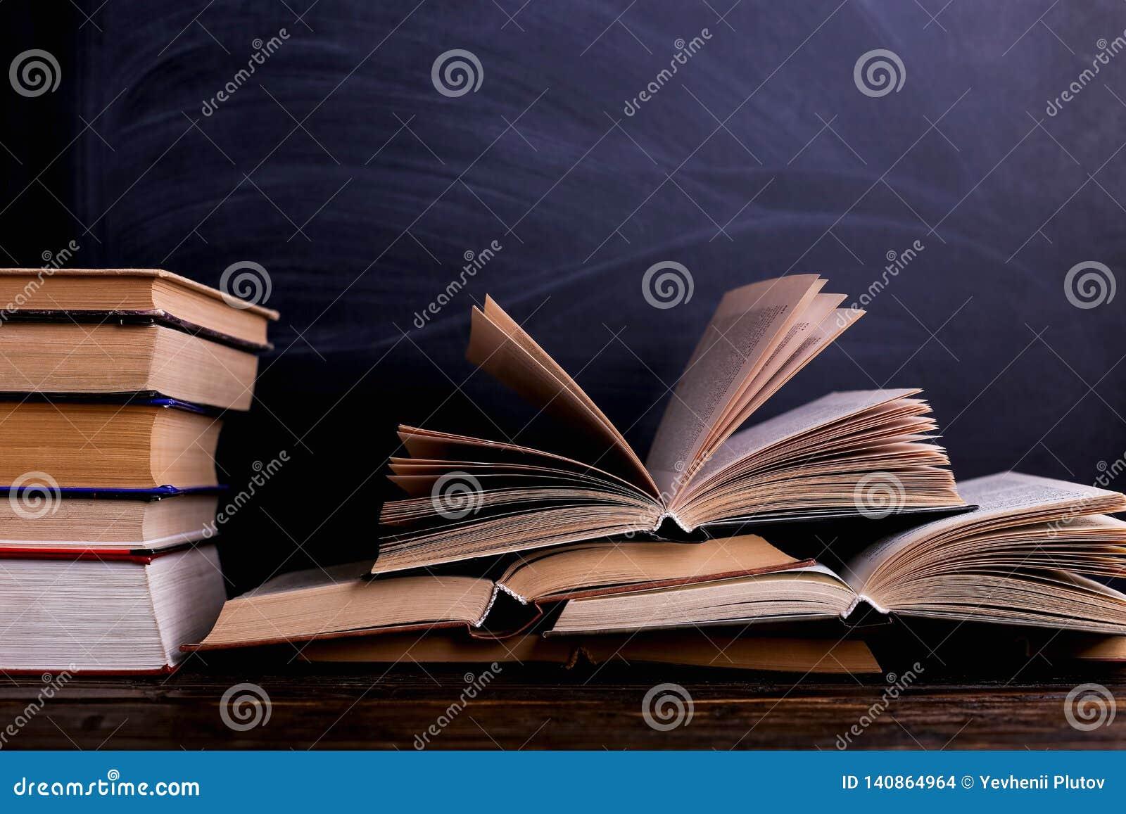 I libri aperti sono una pila sullo scrittorio, contro lo sfondo di un bordo di gesso Compito difficile a scuola, una montagna di