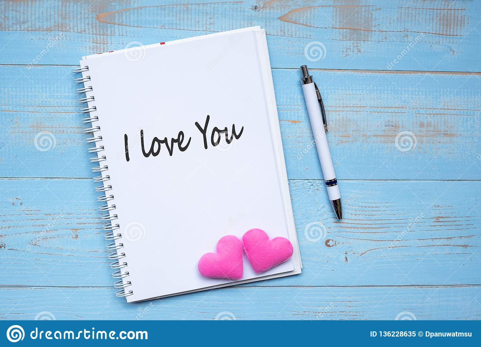 I LOVE YOU word on notebook and pen with couple pink heart shape decoration on blue wooden table background. Wedding, Romantic and