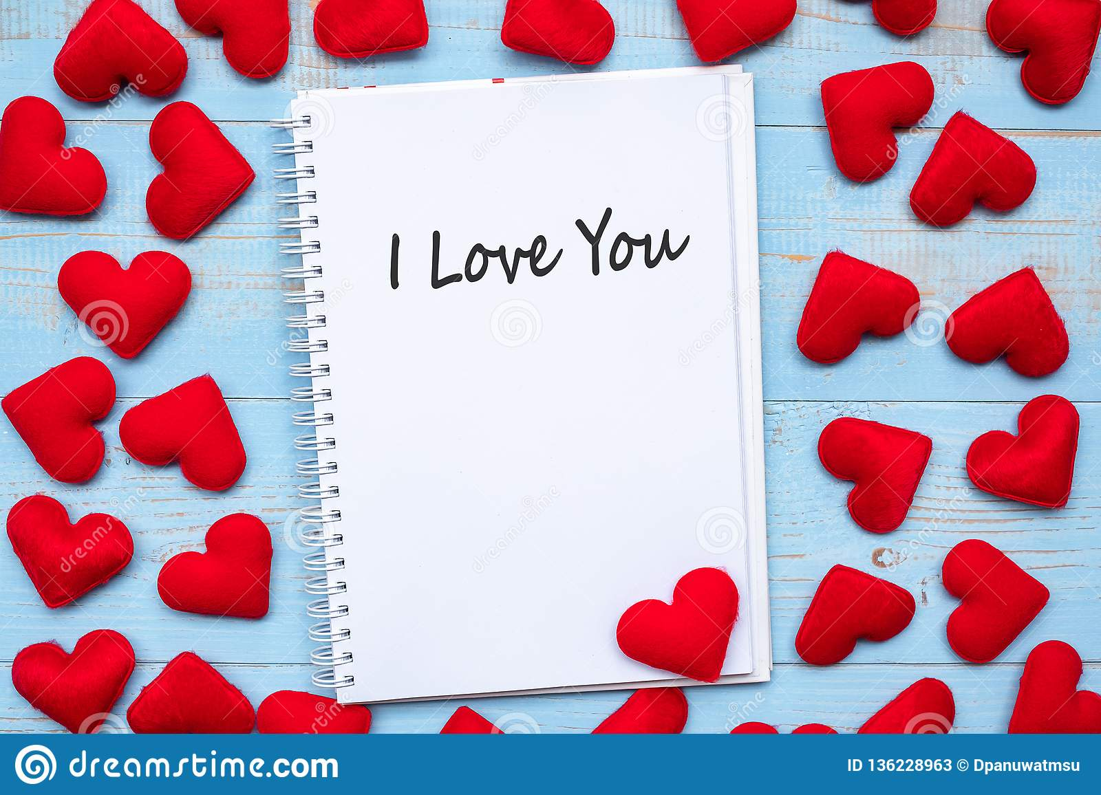 I LOVE YOU word on notebook with pink heart shape decoration on blue wooden table background. Wedding, Romantic and Happy