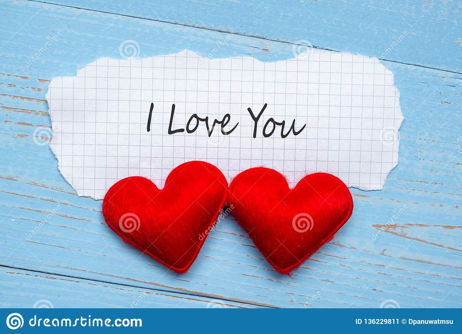 I LOVE YOU word on paper note with couple red heart shape decoration on blue wooden table background. Wedding, Romantic and Happy