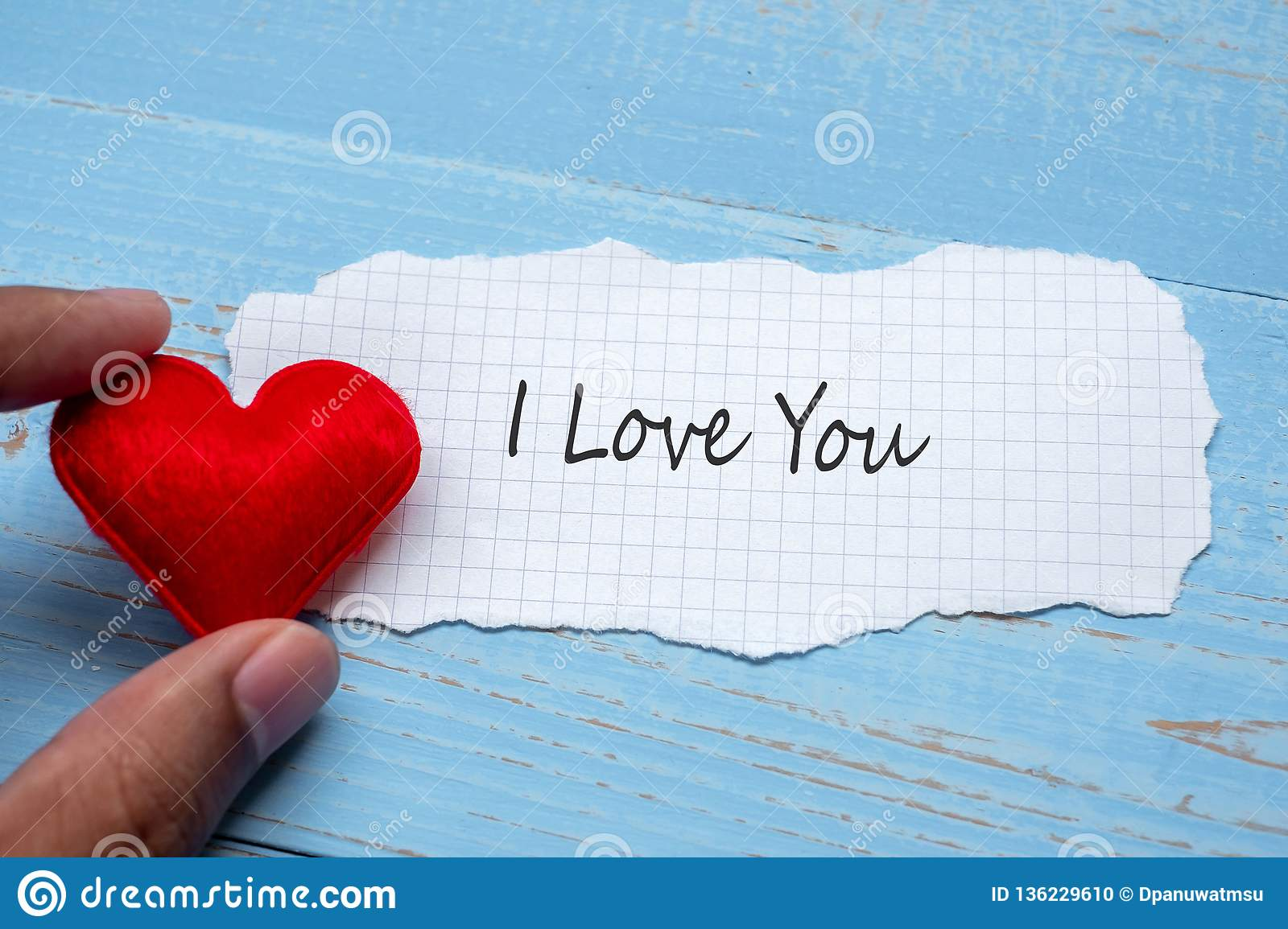 I LOVE YOU word on paper note with red heart shape decoration on blue wooden table background. Wedding, Romantic and Happy