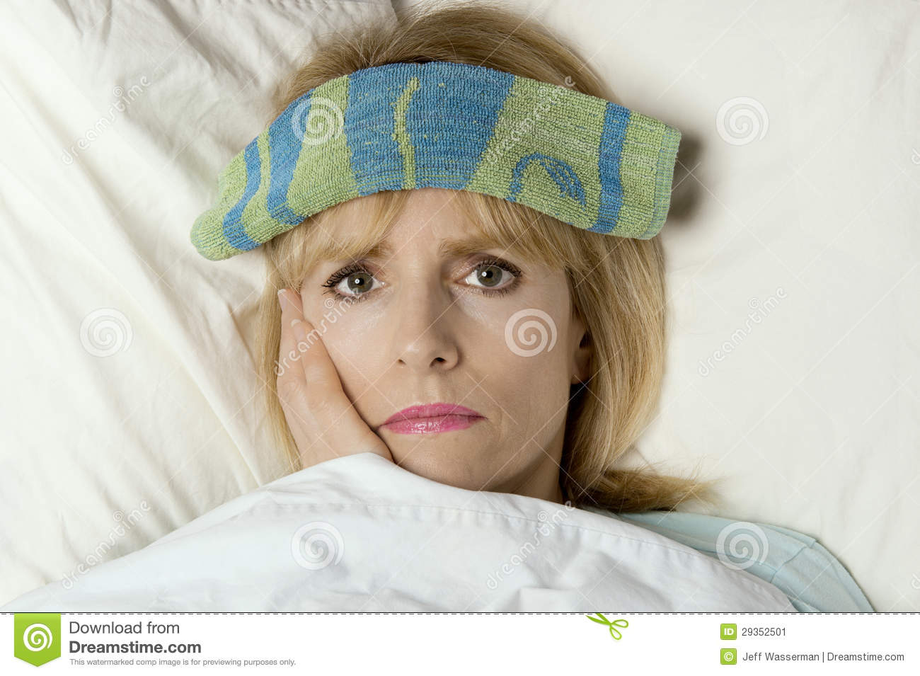 Woman sick in bed or hospital with thermometer in mouth and washcloth ...