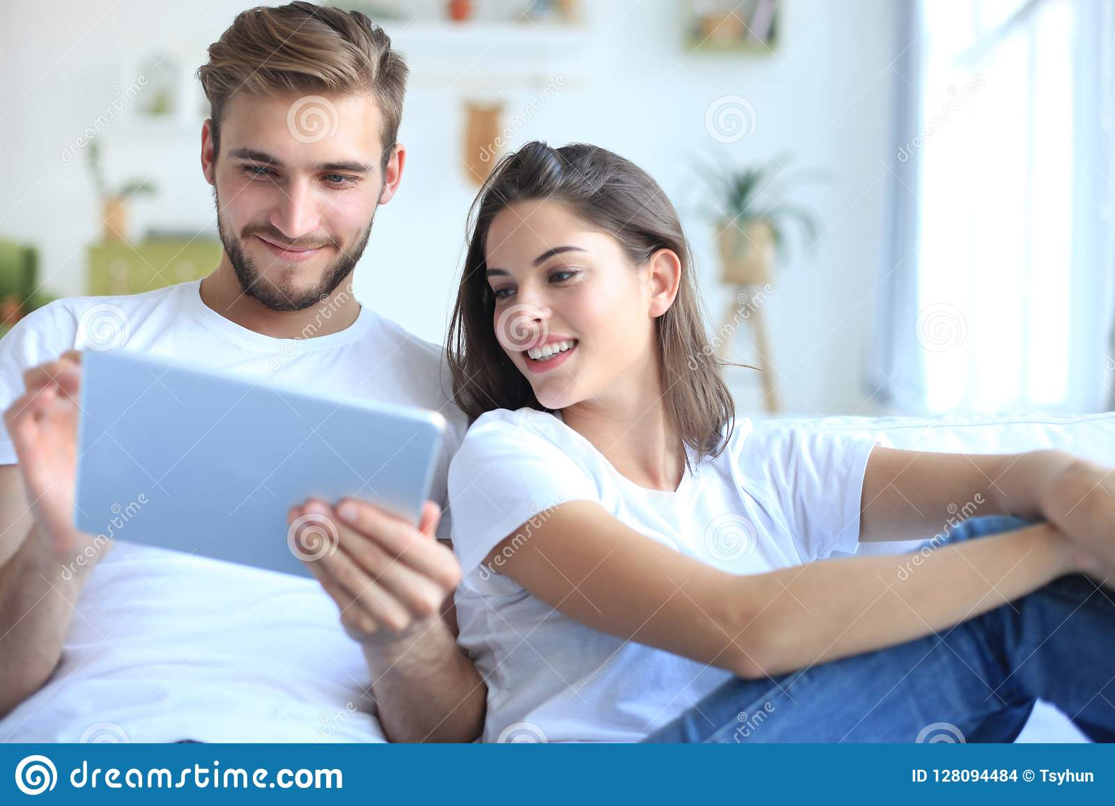 I media di sorveglianza delle giovani coppie soddisfanno online in una compressa che si siede su un sofà nel salone