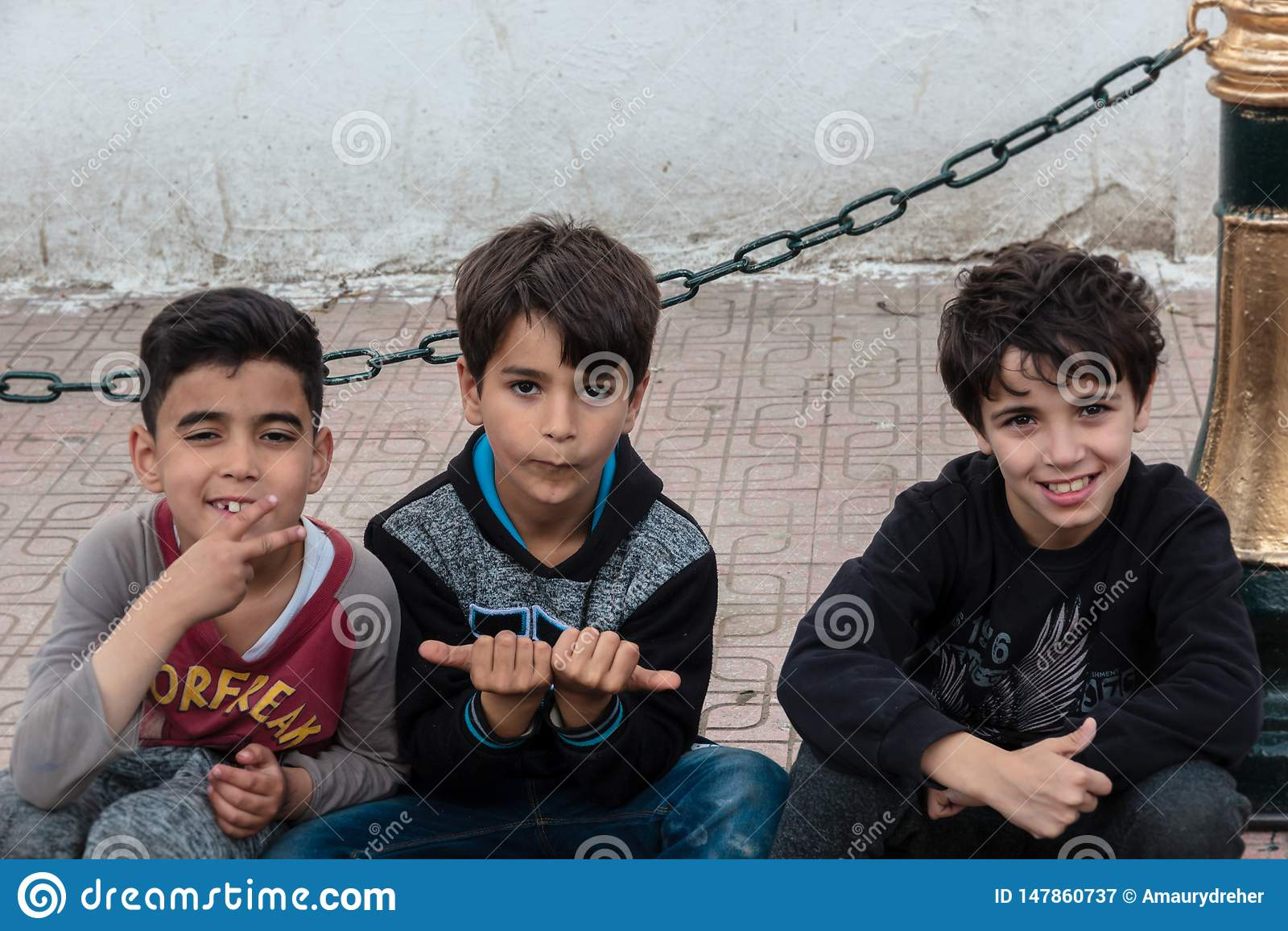 Three algerian boys smiling at me