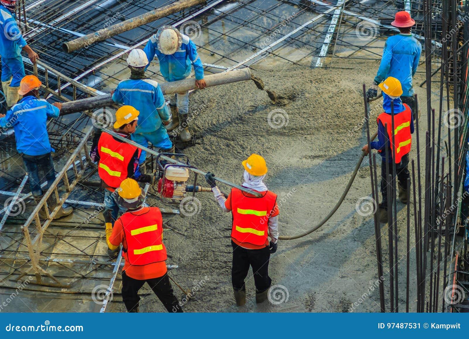 I muratori che per mezzo di un motore a benzina del vibratore per calcestruzzo scrivono al cantiere per comprimere il calcestruzz