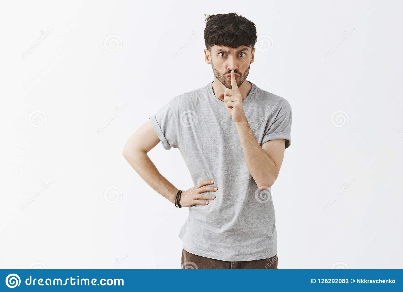 I order you keep quiet. Serious displeased and strict aduly male teacher with stylish hairstyle and beard saying shh