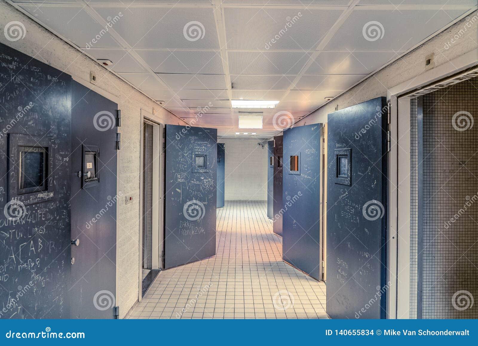 I PAESI BASSI 24 FEBBRAIO: Un corridoio vuoto di una prigione con le mattonelle sul pavimento ed aprire le porte d acciaio delle