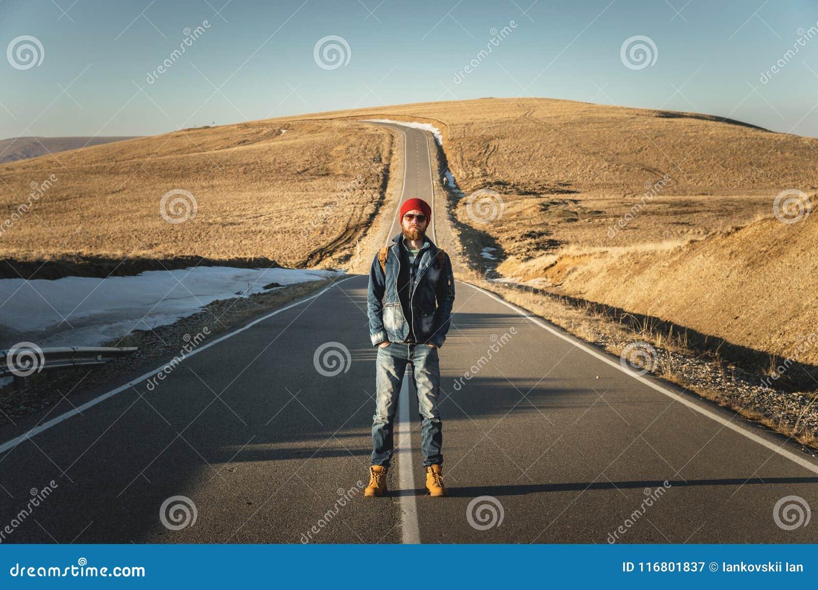 I pantaloni a vita bassa barbuti alla moda in occhiali da sole con uno zaino d annata stanno su un asfalto della strada campestre