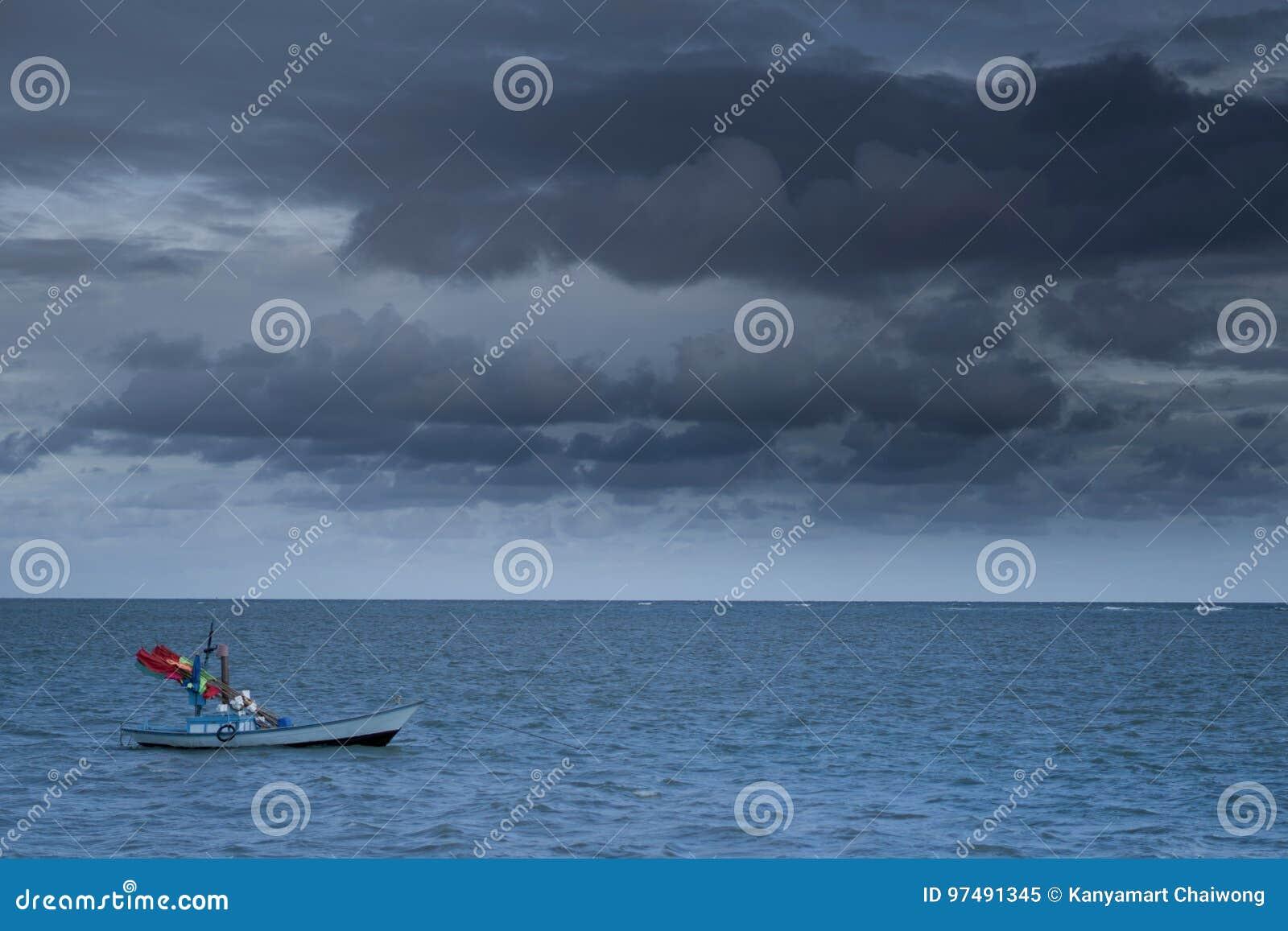 I pescherecci galleggiano sul mare nella venuta scura della tempesta e del cielo