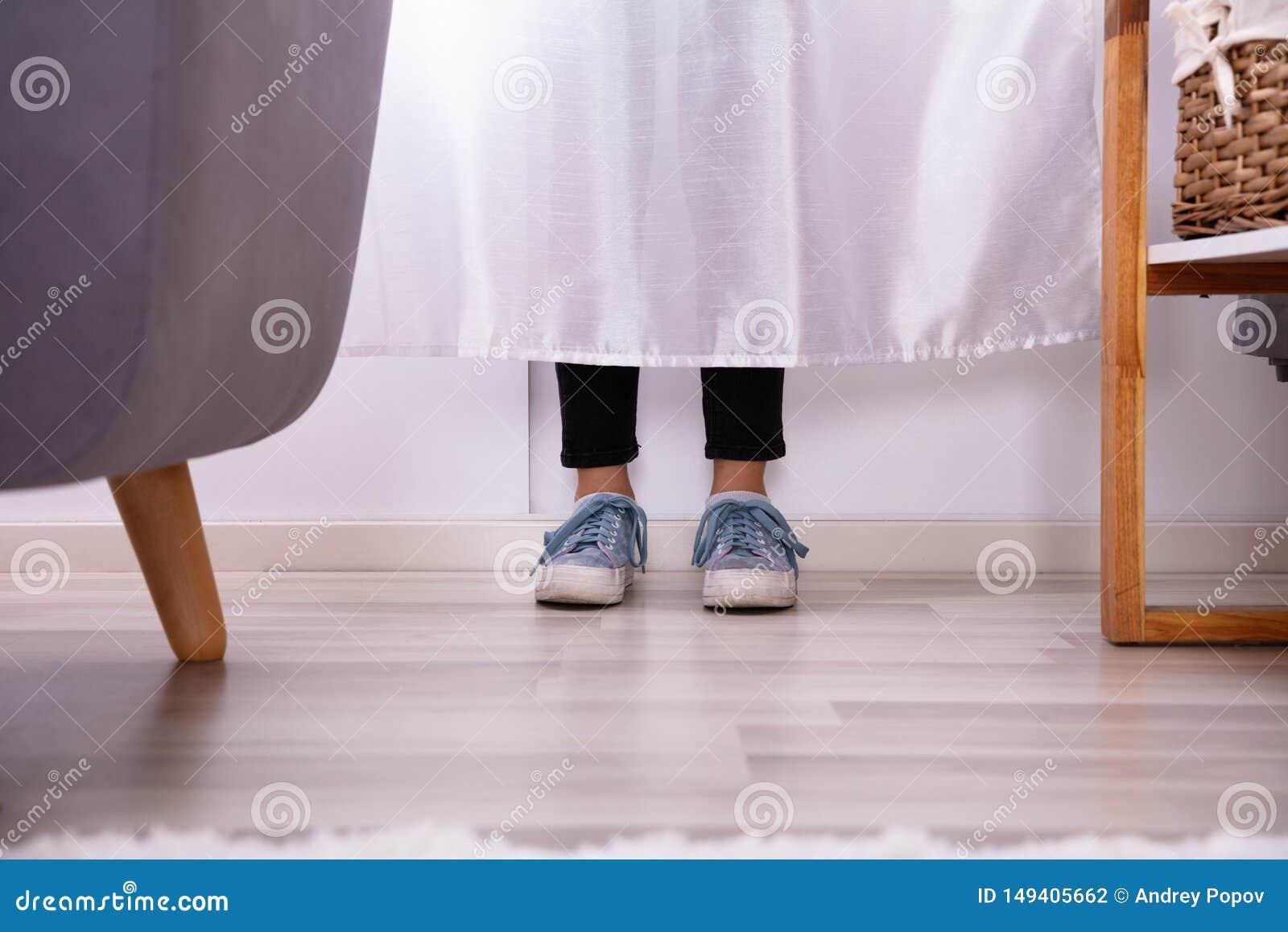 I piedi della ragazza dietro la tenda