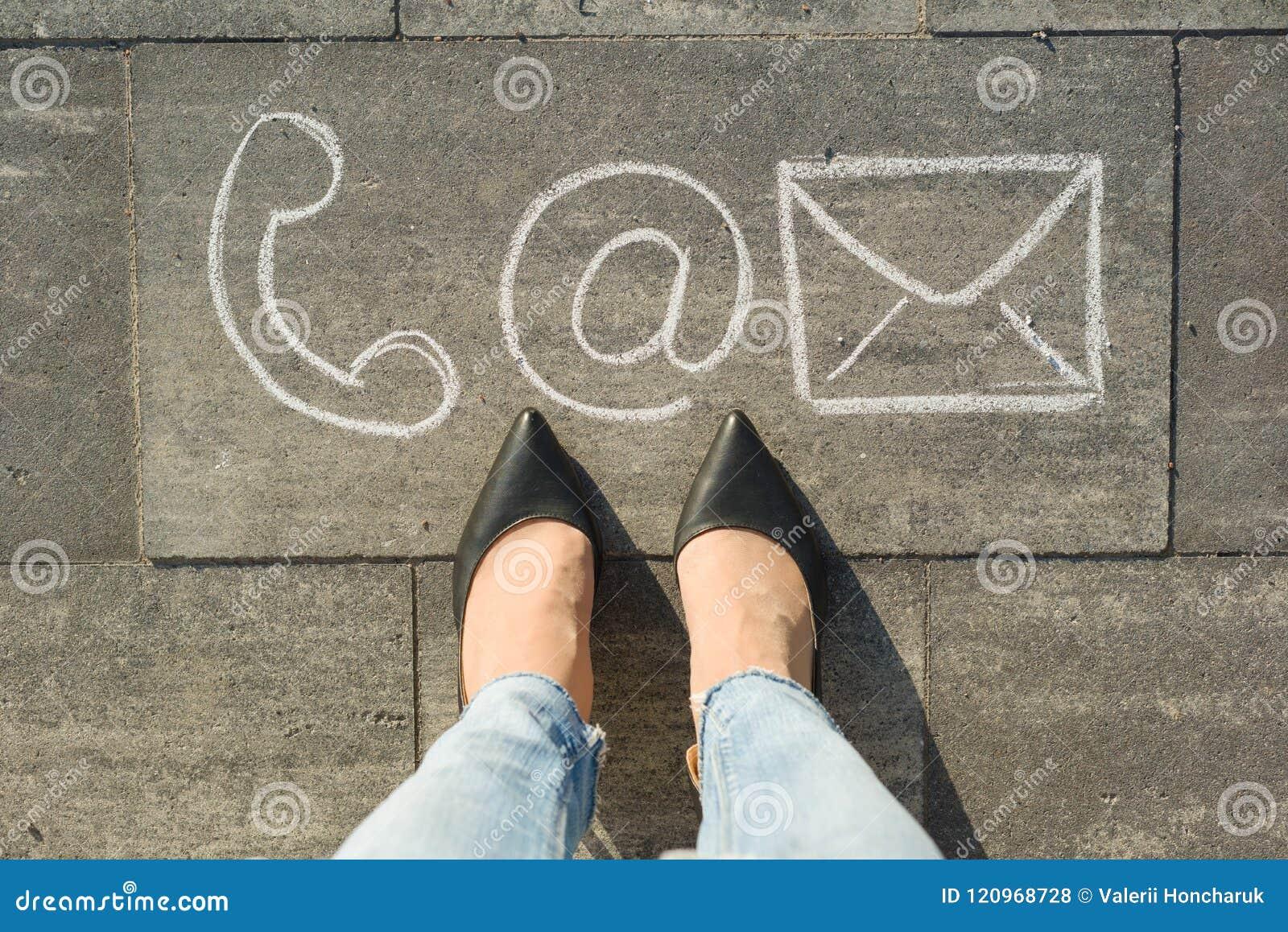 I piedi femminili con i simboli del contatto telefonano la posta e la lettera, scritte sul marciapiede grigio, comunicazione o ci